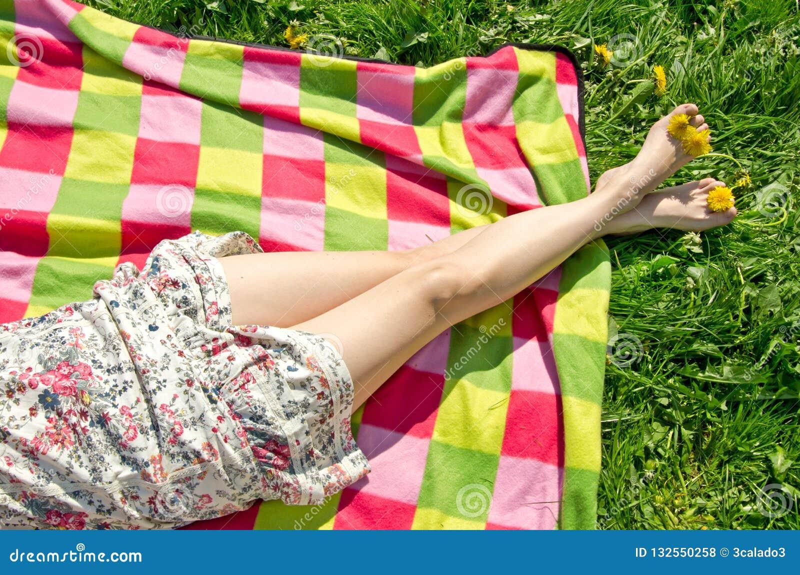 Ben av en härlig ung kvinna i sommarklänning på den färgrika picknickfilten
