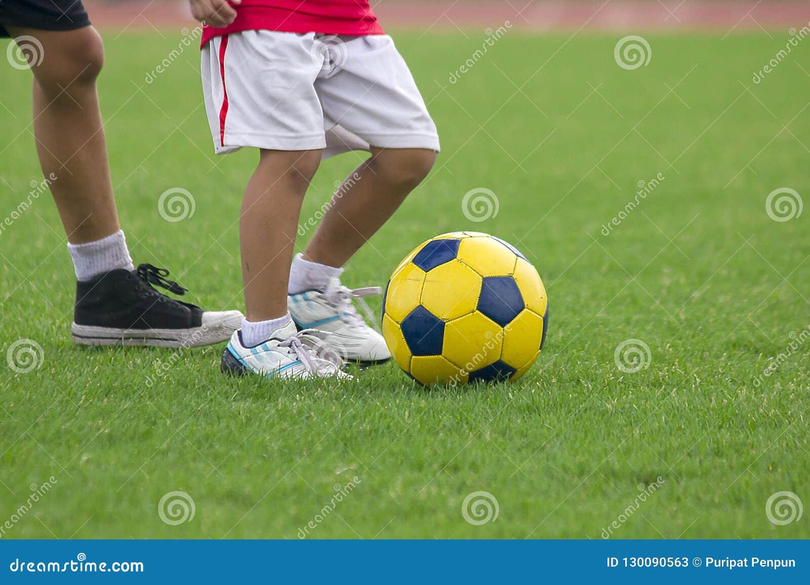 Ben av ungar sparkar fotboll