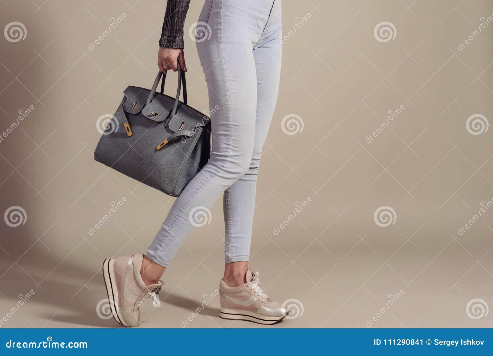 Ben för bakgrundspåsebegrepp som shoppar den vita kvinnan flickan i jeans och gymnastikskor rymmer en trendig stor påsecloseup me