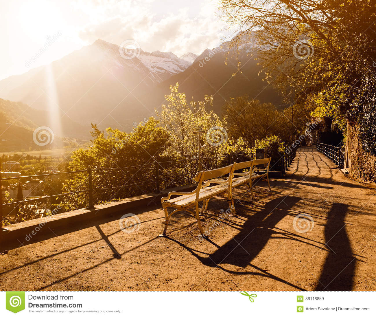 A bench in front of the hills during sunset
