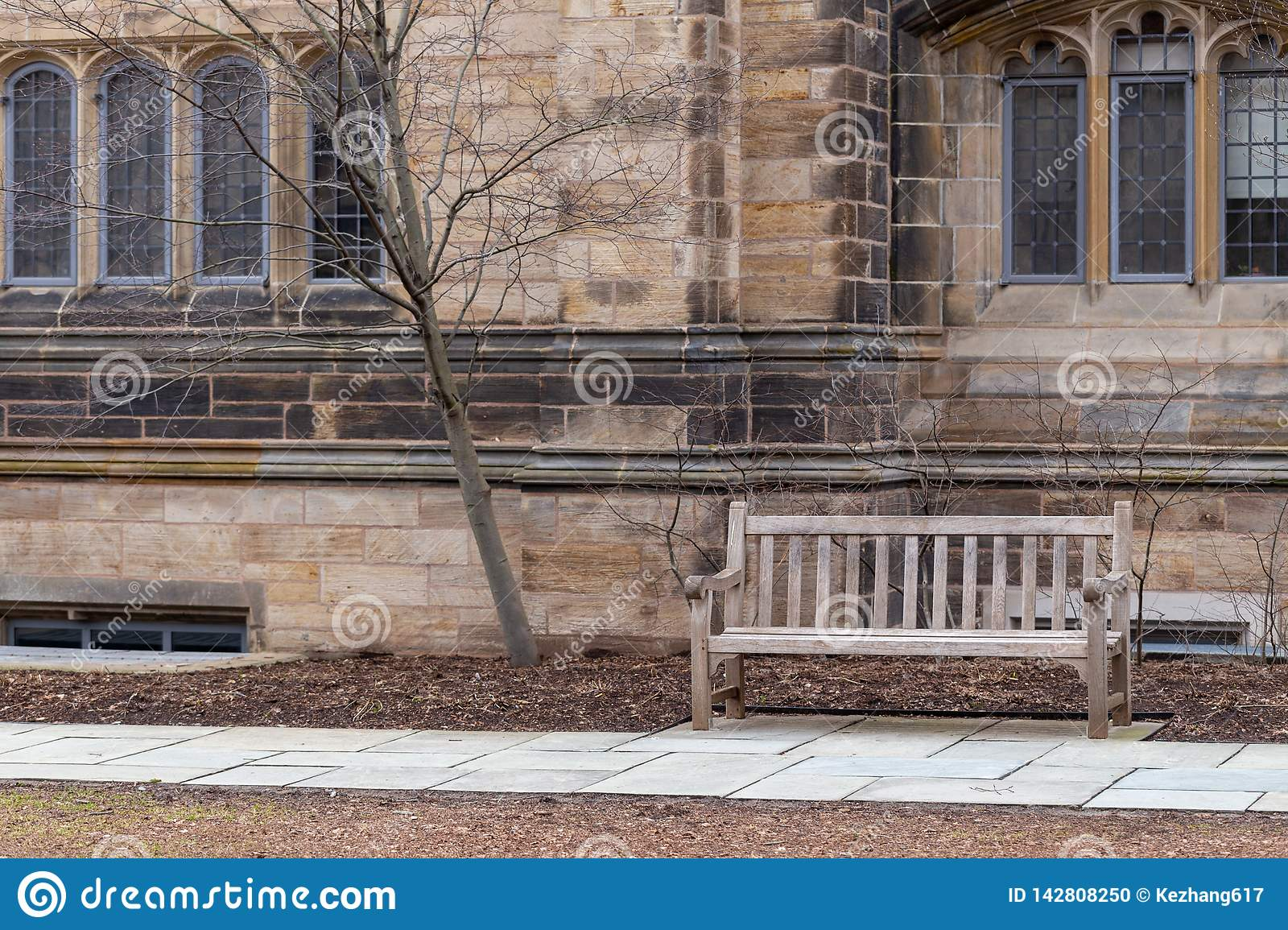 Bench on stone walkway against old decorative building