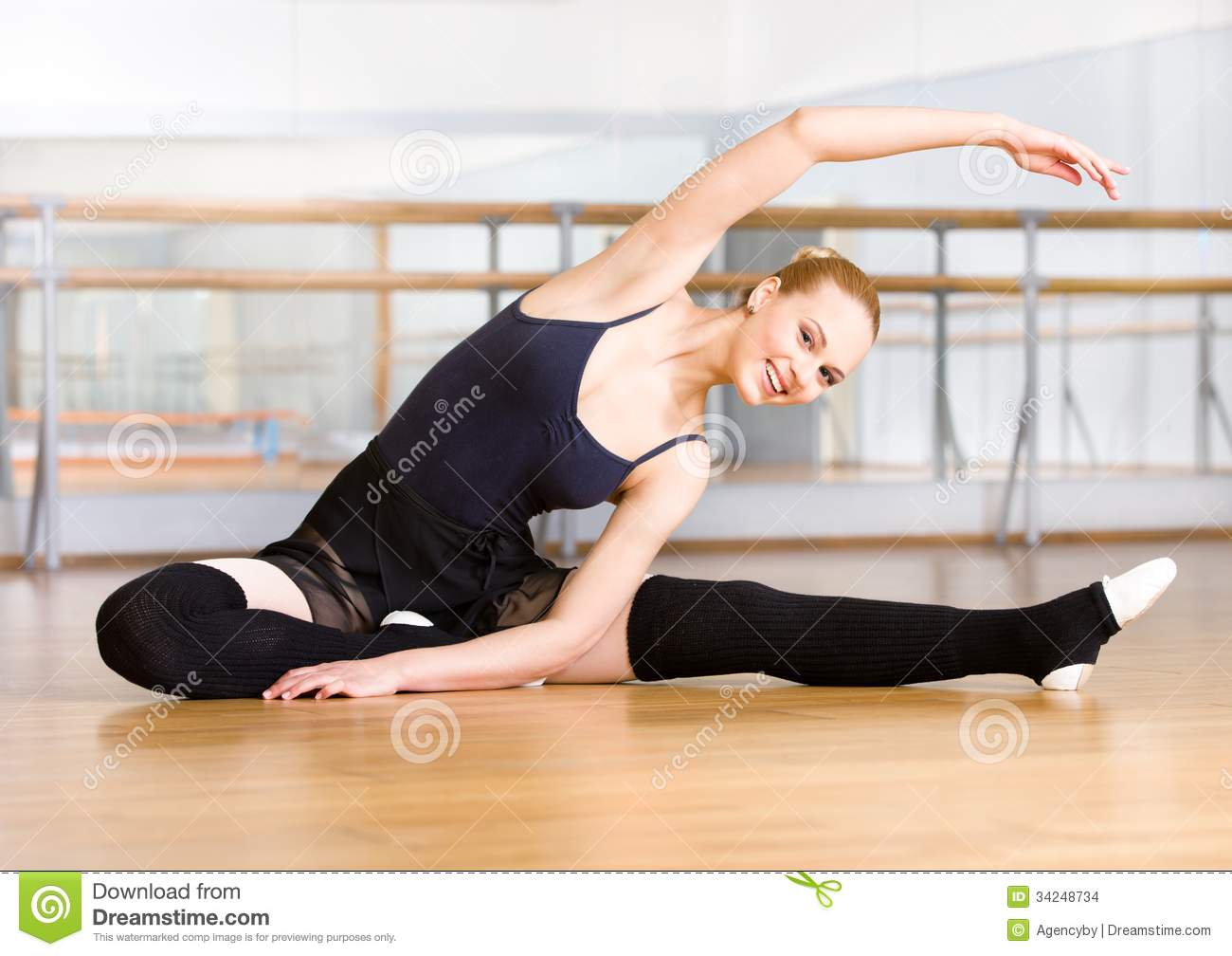 Bending ballet dancer stretches herself on the floor stock for On the floor on the floor