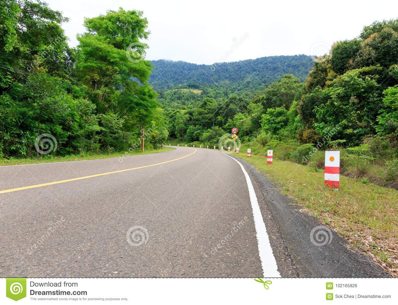 Bending Road to the Top of a Mountain with Green Trees and Traffic Signs