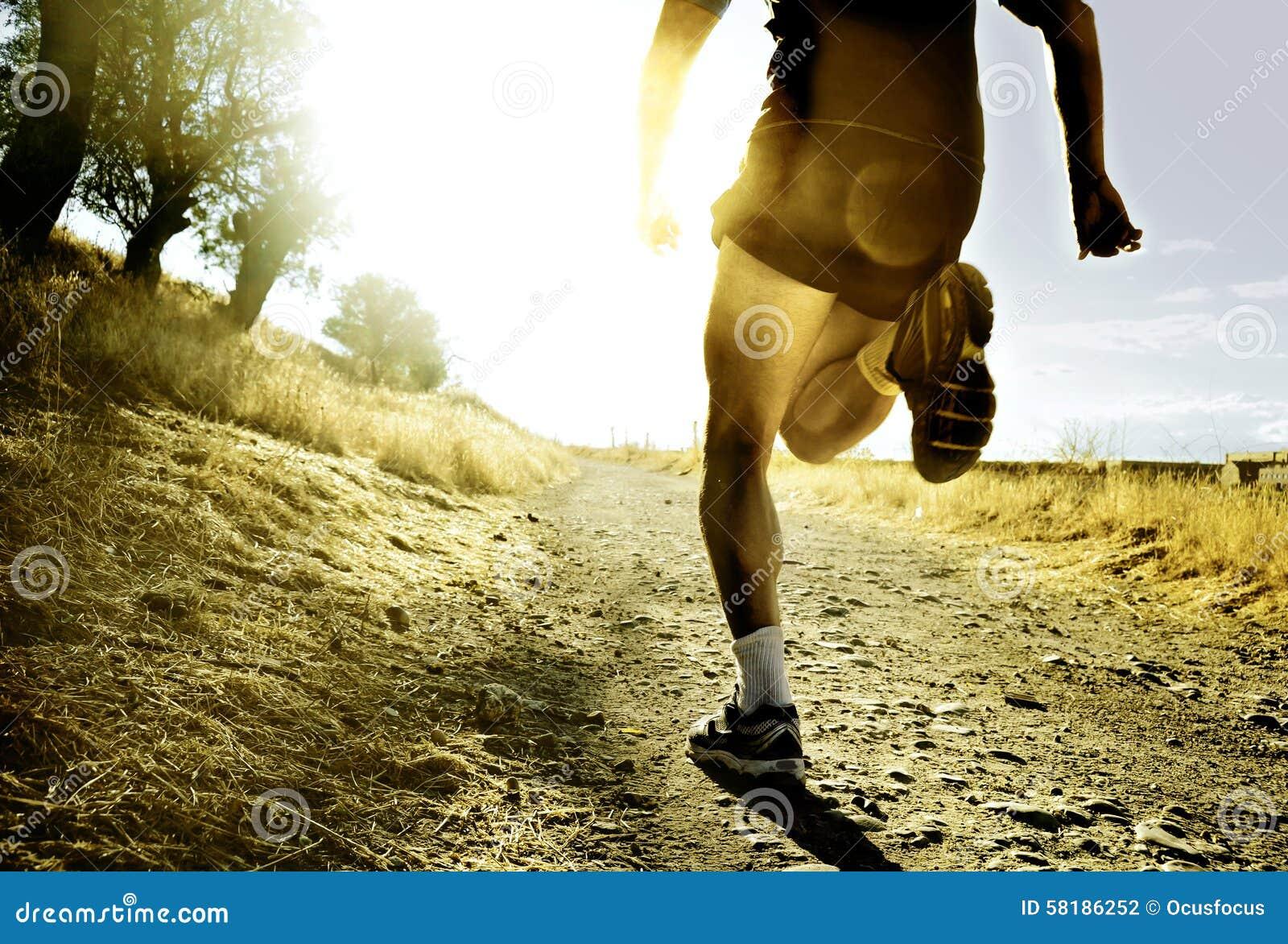Benen en voeten extreme dwars de mens van het land lopende opleidings bij plattelandszonsondergang