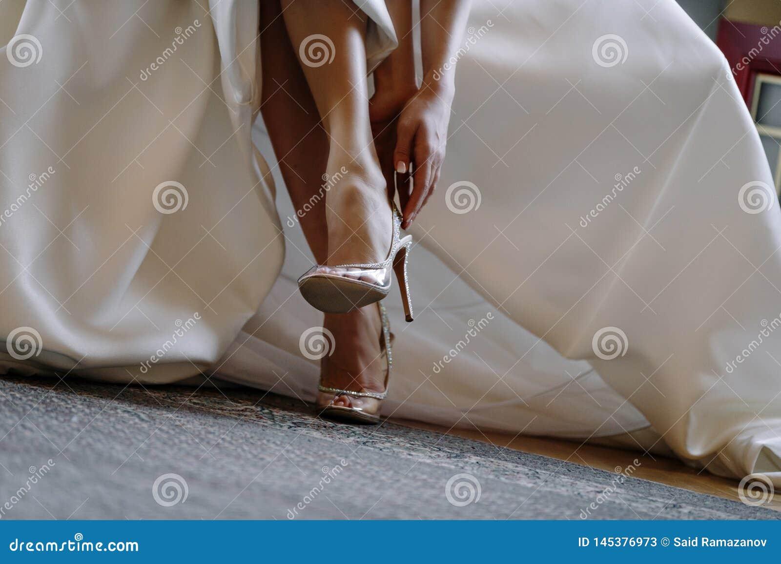 Benen van de bruid in elegante schoenen