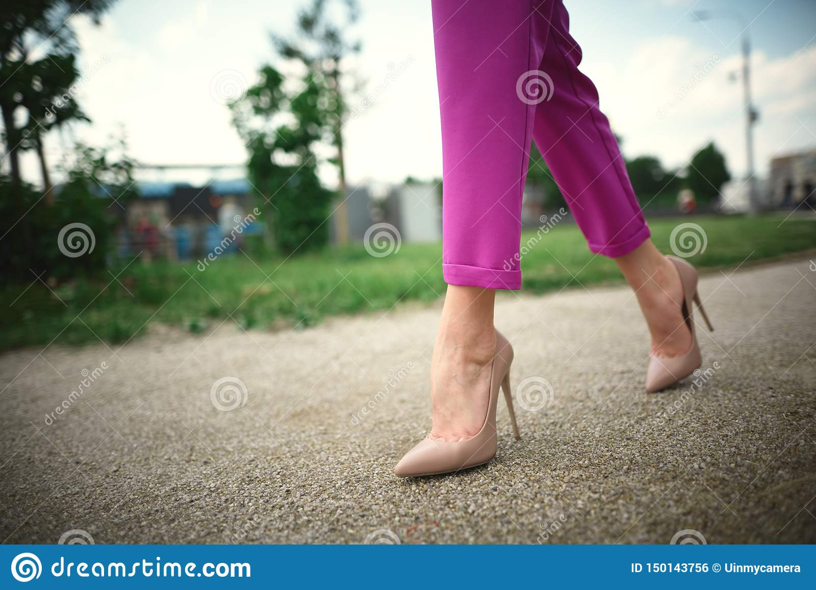 Benen van een jong meisje in hielen in stap op grasachtergrond