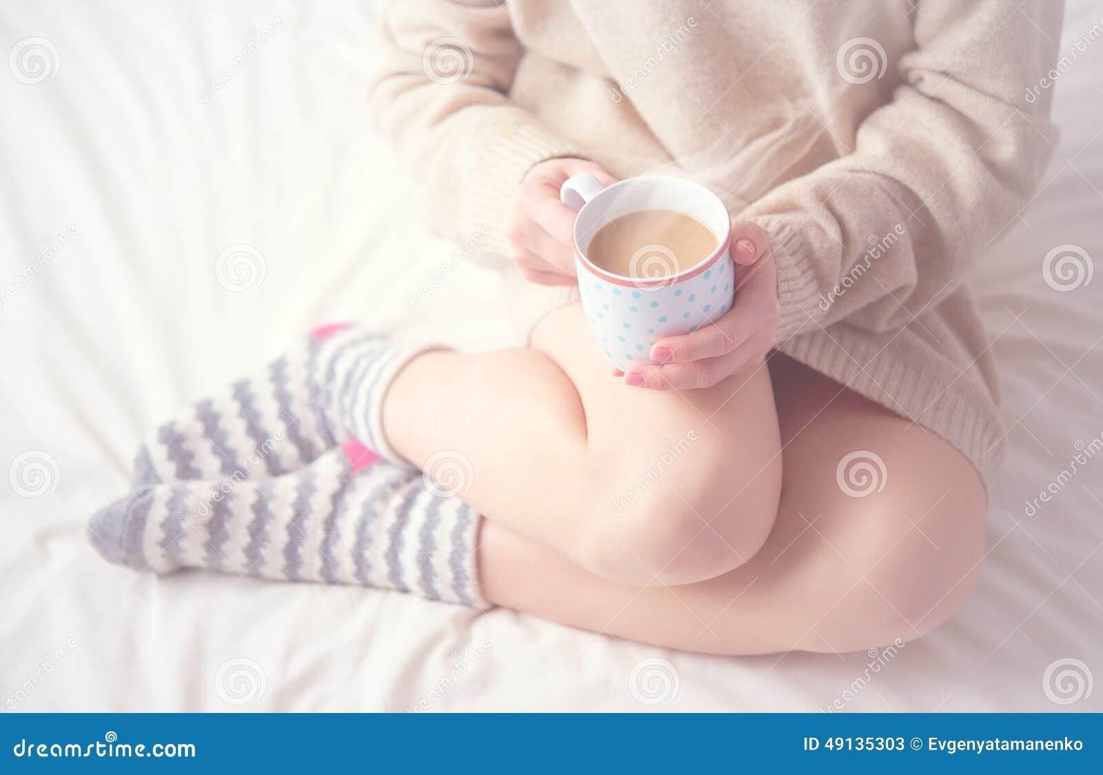 Benen van meisjes warme wollen sokken en kop van koffie het verwarmen, de winterochtend in bed