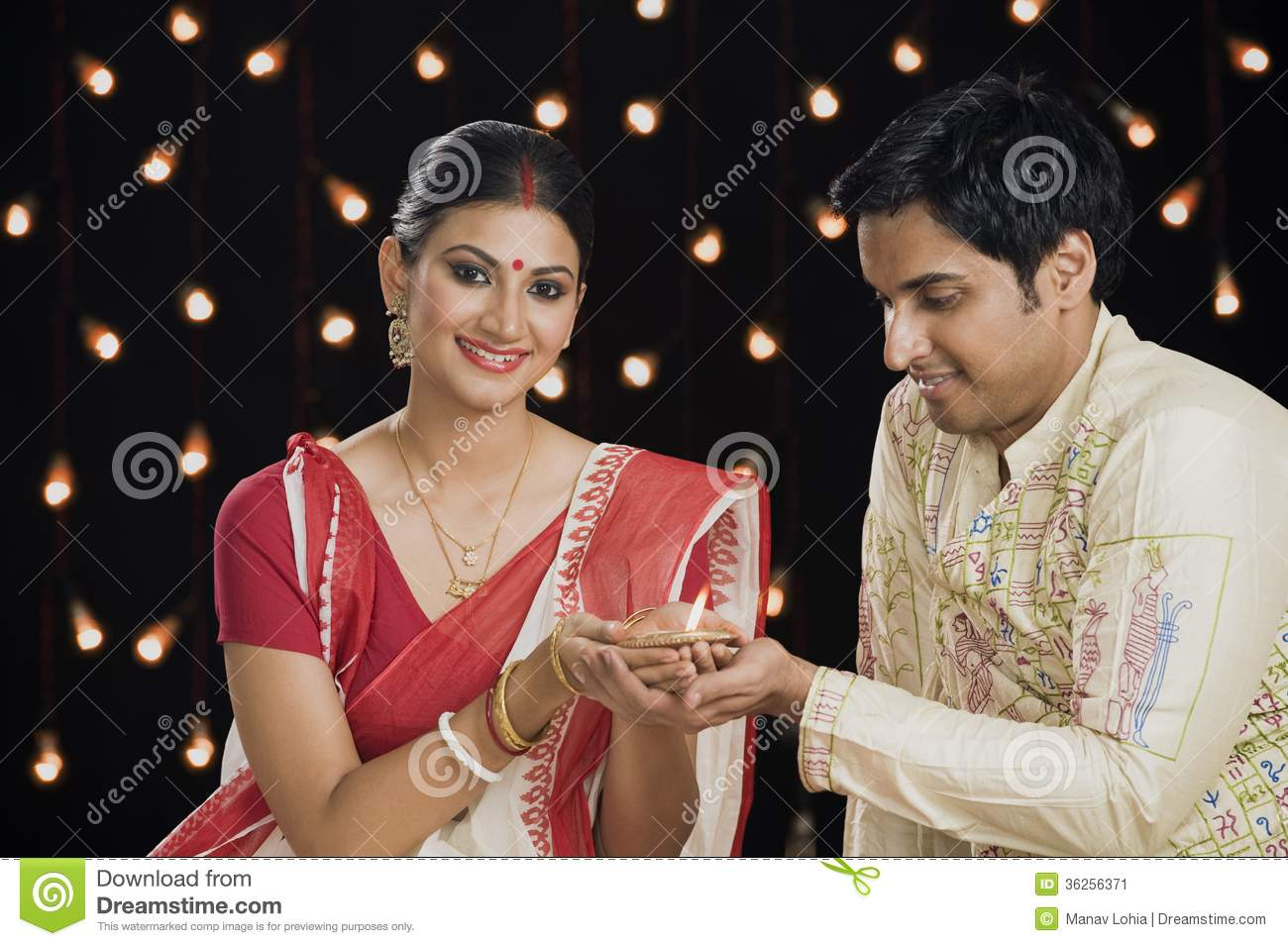 Bengali couple holding an oil lamp together and smiling stock image