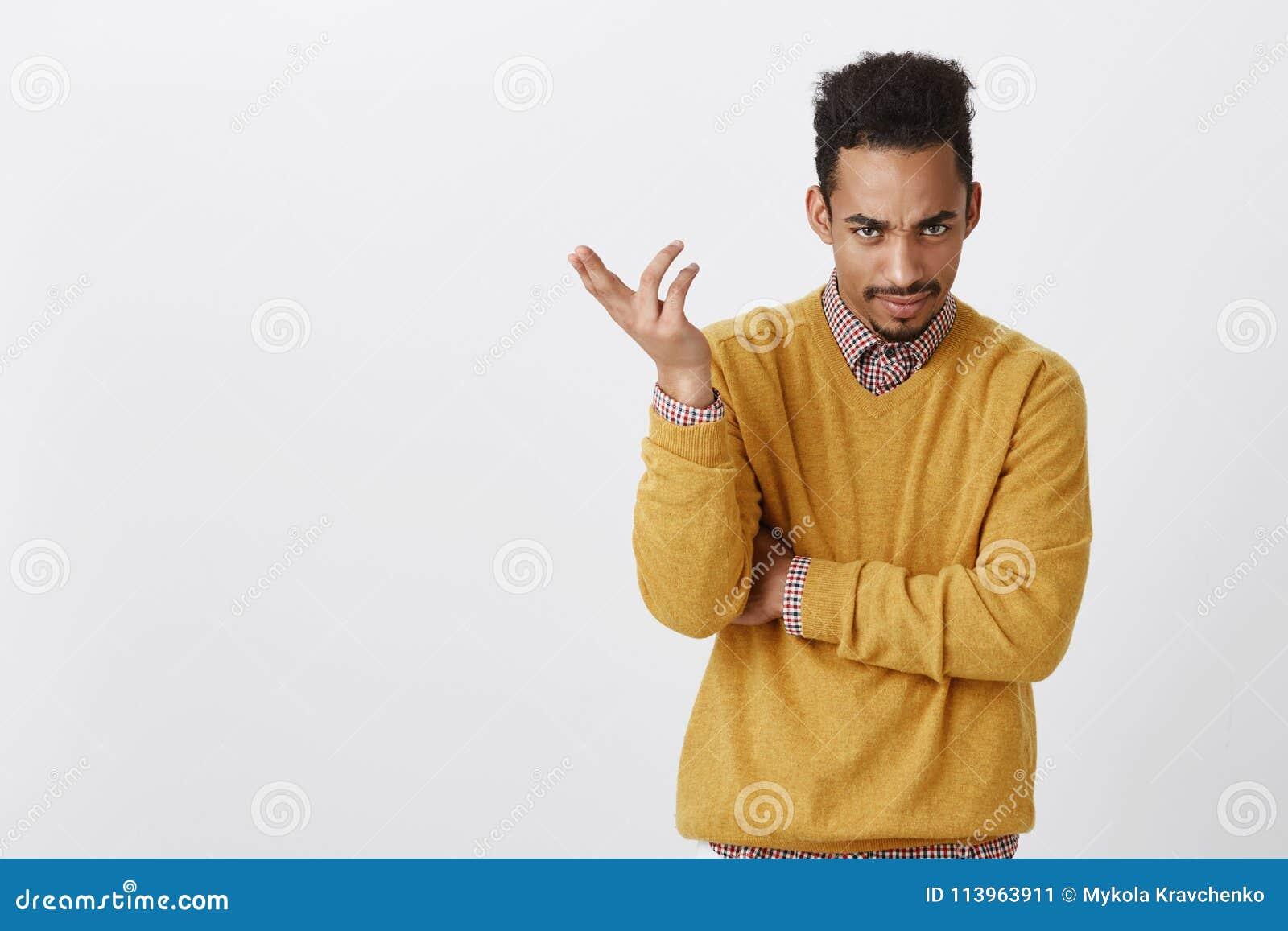 Bent stom u Portret van geërgerd knap mannetje met afrokapsel in gele kleren, het gesturing, die verwarring uitdrukken