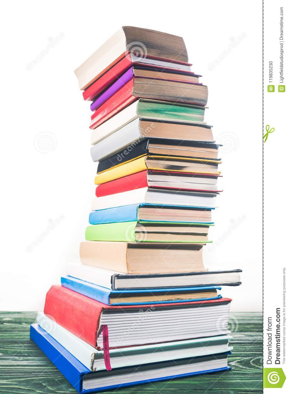 Bent tower of stacked books on white background