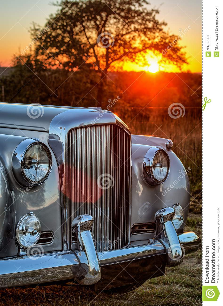Verticle close up front view of vintage luxery limousine with sunset behind.