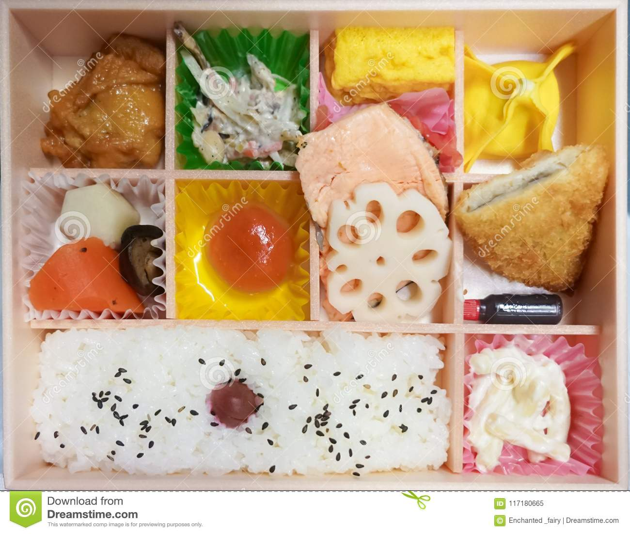 Bento box. Bento is Japanese traditional takeaway lunch box divided into small section with various food and Japanese sweet i
