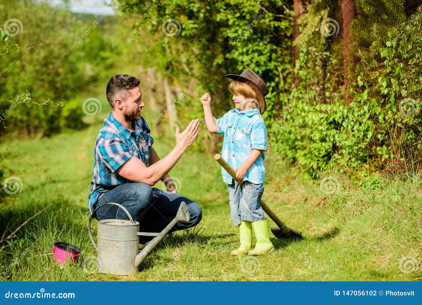Benutzen Sie Gießkanne und Topf Gartenger?te Vater und Sohn im Cowboyhut auf Ranch Eco-Bauernhof Gl?cklicher Tag der Erde familie
