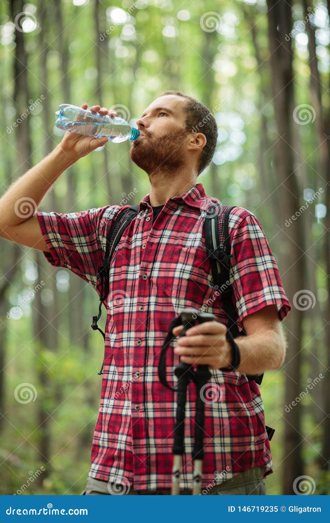 Bepaalde jonge mens die door bos, drinkwater en het rusten wandelen