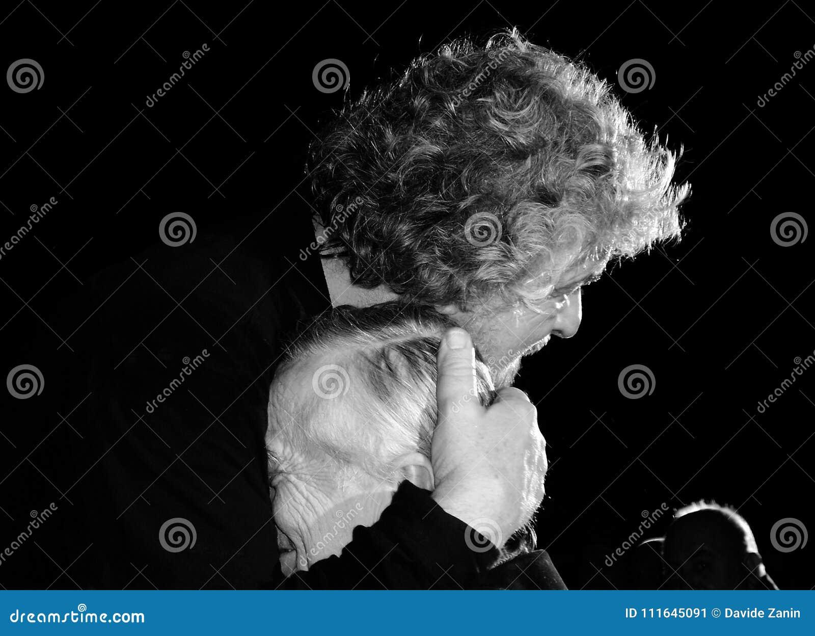 Beppe Grillo omhelst affectionately een bejaarde persoon