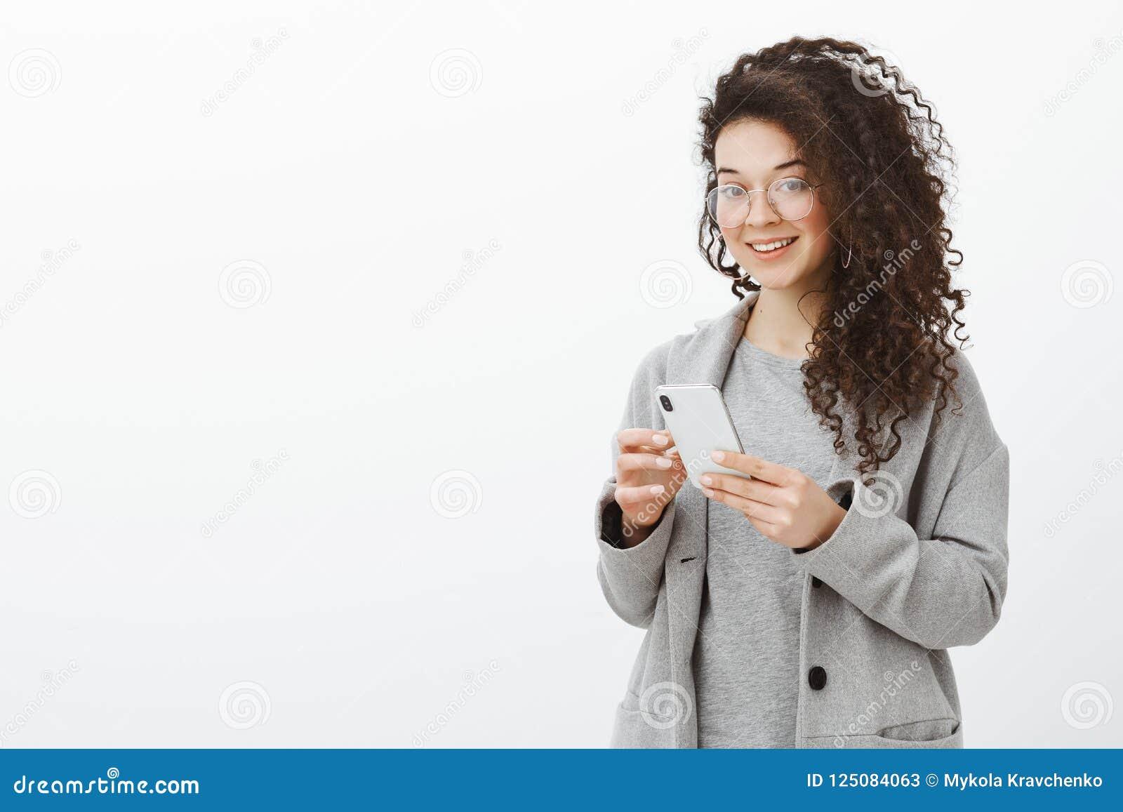 Berätta mig ditt telefonnummer Stående av den stilfulla snygga säkra kvinnan i moderiktiga exponeringsglas och grå färglag som ry