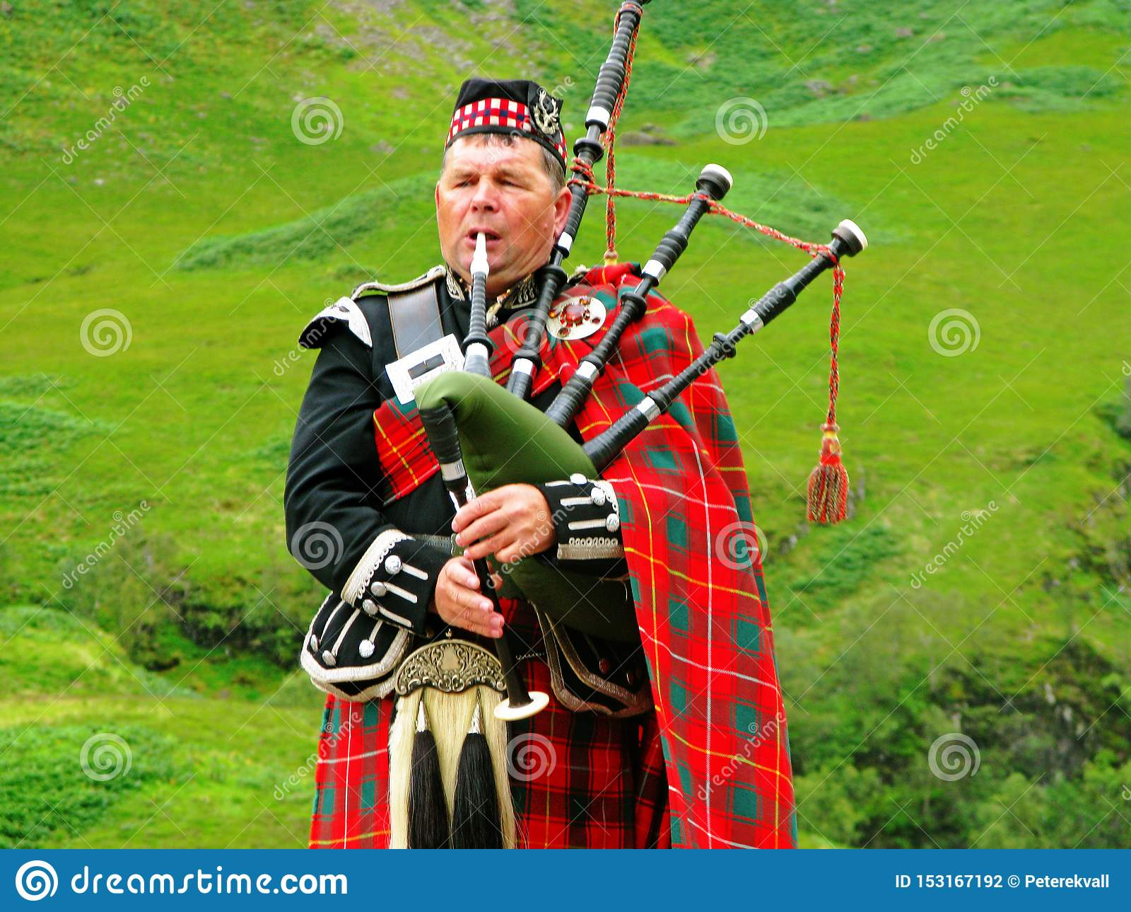 Berömd säckpipe- musiker som bär traditionell kläder