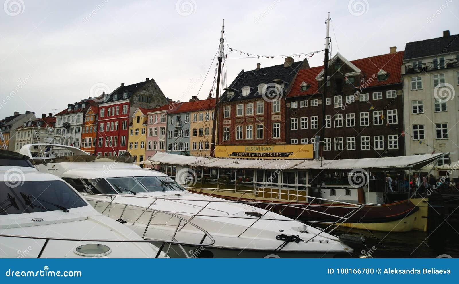 Berömda Nyhavn i Köpenhamn, med restauranger och dyra fartyg på vattnet