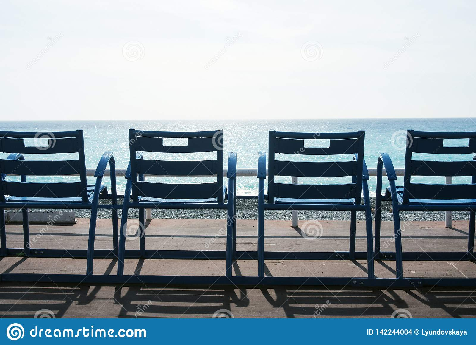 Berühmte blaue Stühle auf Promenade des Anglais von Nizza, Frankreich gegen den Hintergrund des blauen Meeres