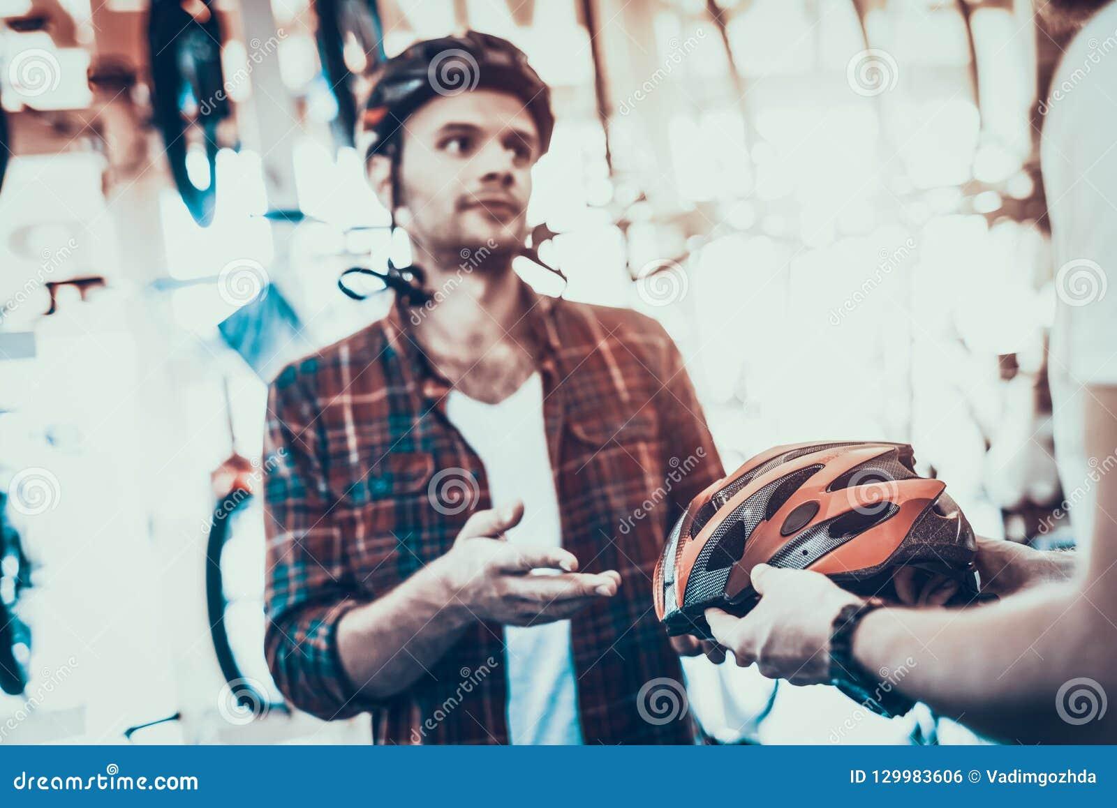 Berater Helps Guy Choose Helmet für Fahrrad-Fahrten