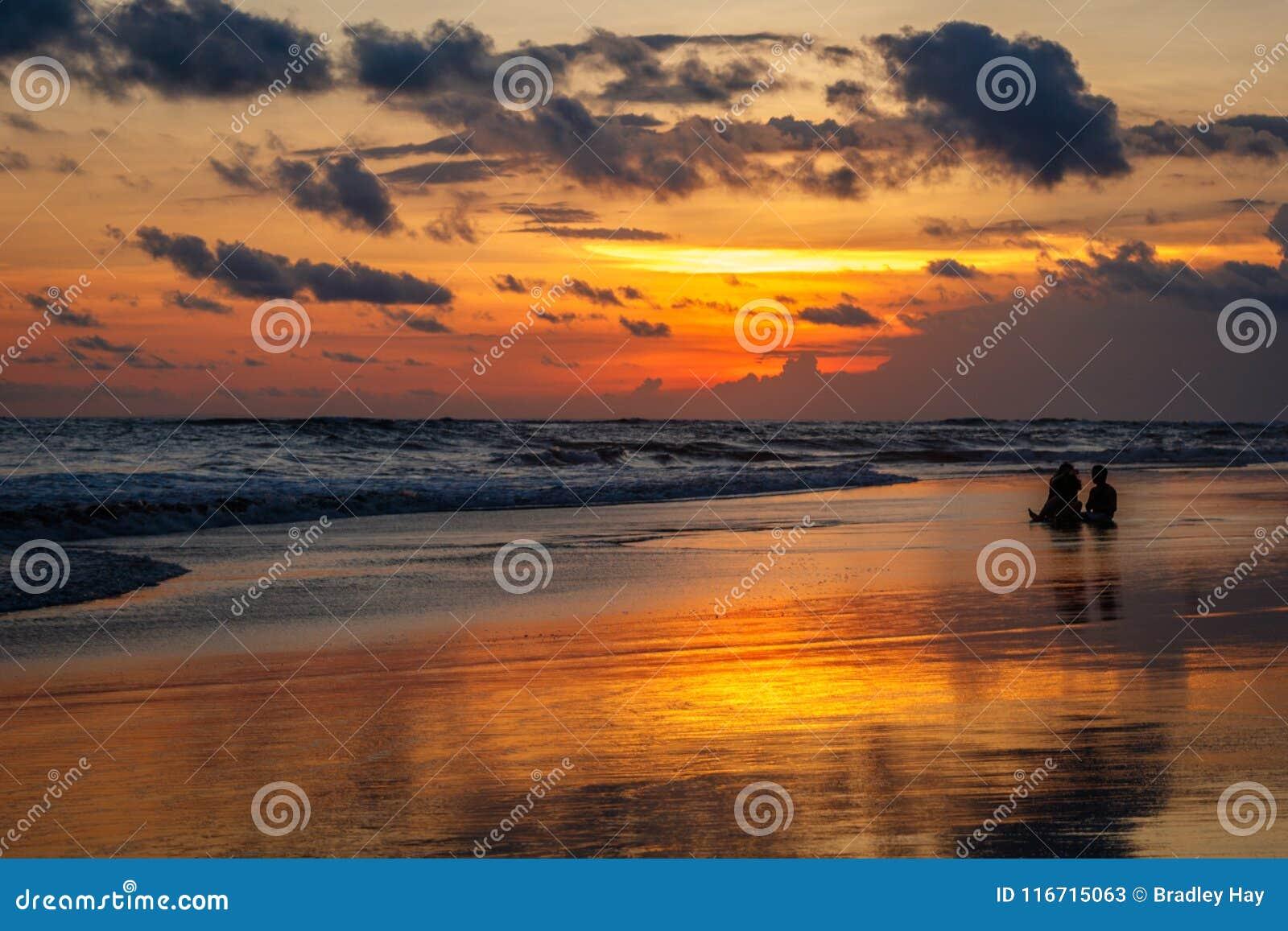 Berawa beach Pantai Berawa at sunset. Silhouettes of two people sitting in the tide. Canggu, Bali, Indonesia.