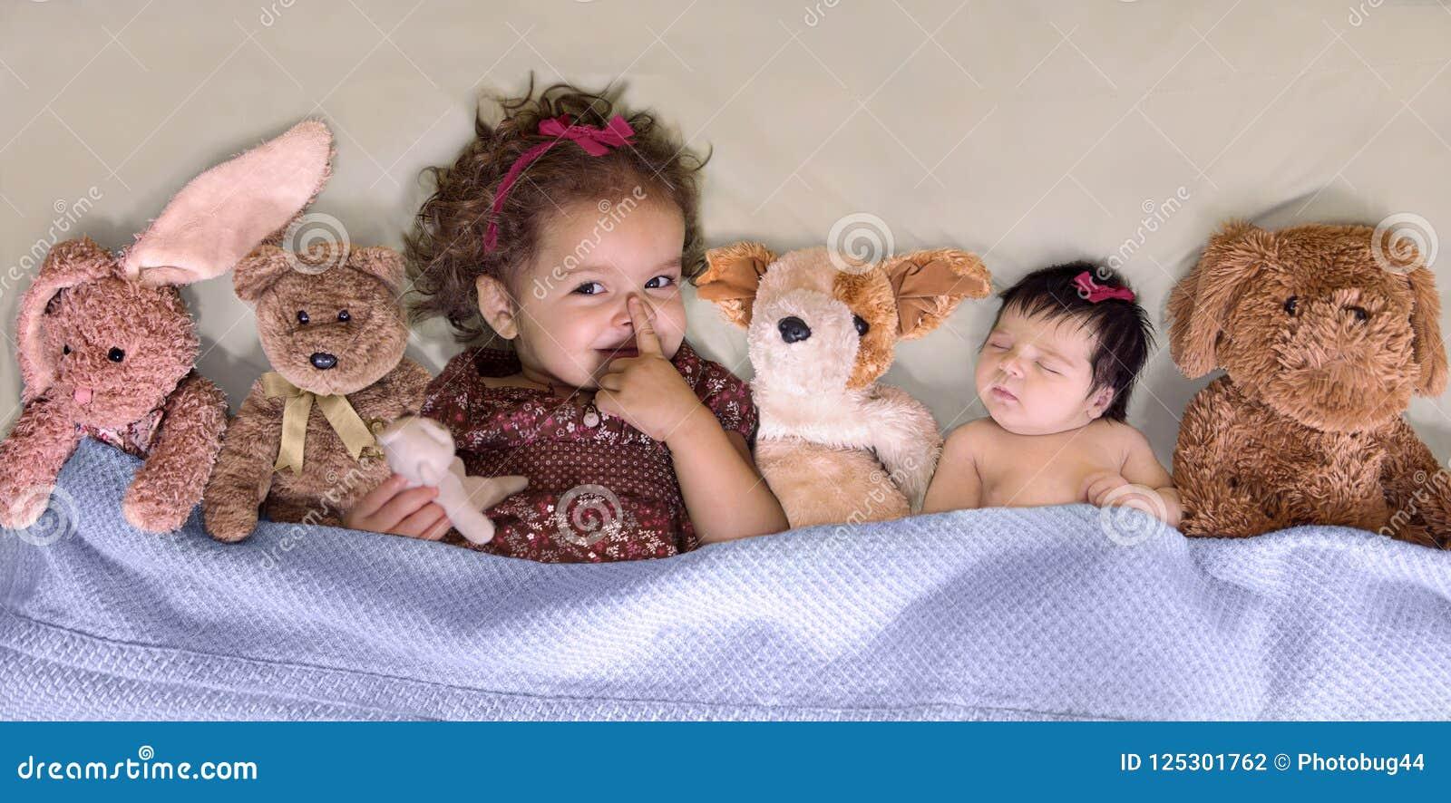 Berbeć dziewczyna gestykuluje dla zaciszności podczas gdy dziecko siostra śpi