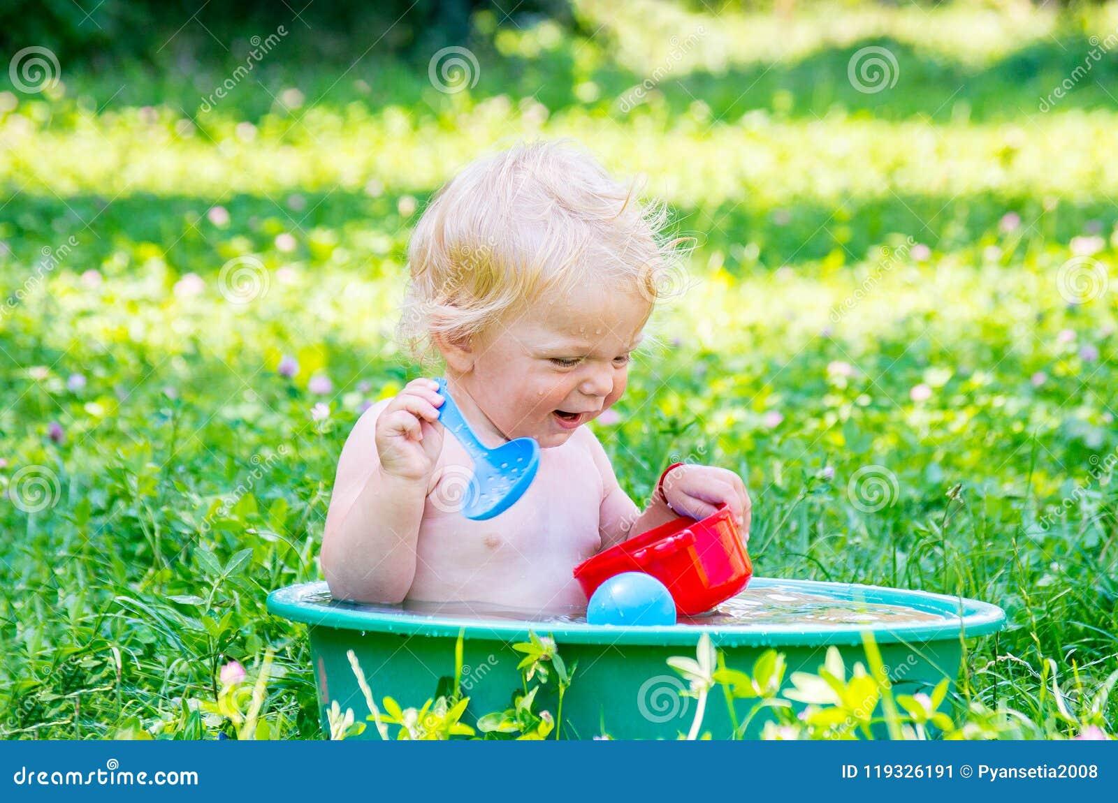 Berbeć dziewczynka z niebieskimi oczami ma zabawę z wodą