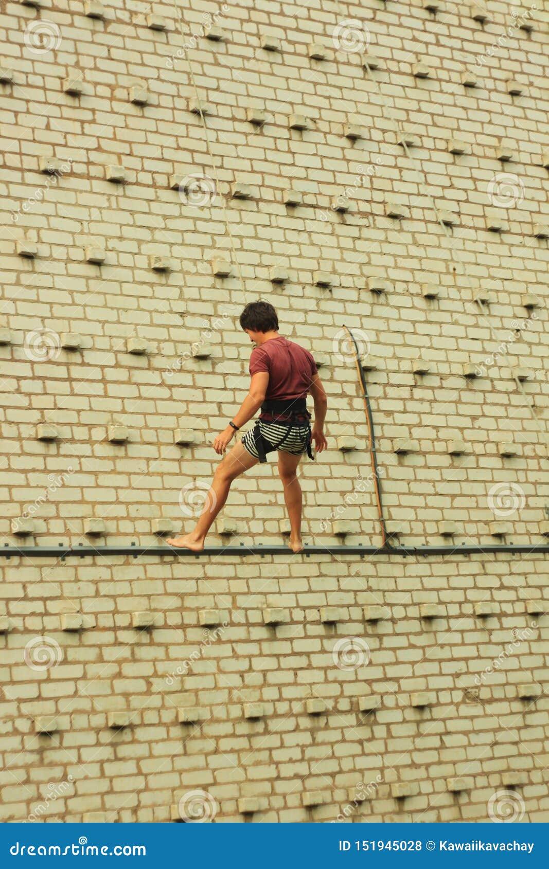 Berdyansk/de Oekraïne - JUNI 22, 2019: Een mensentreinen van de rotsklimmer bij de het beklimmen muur Actieve en gezonde levensst