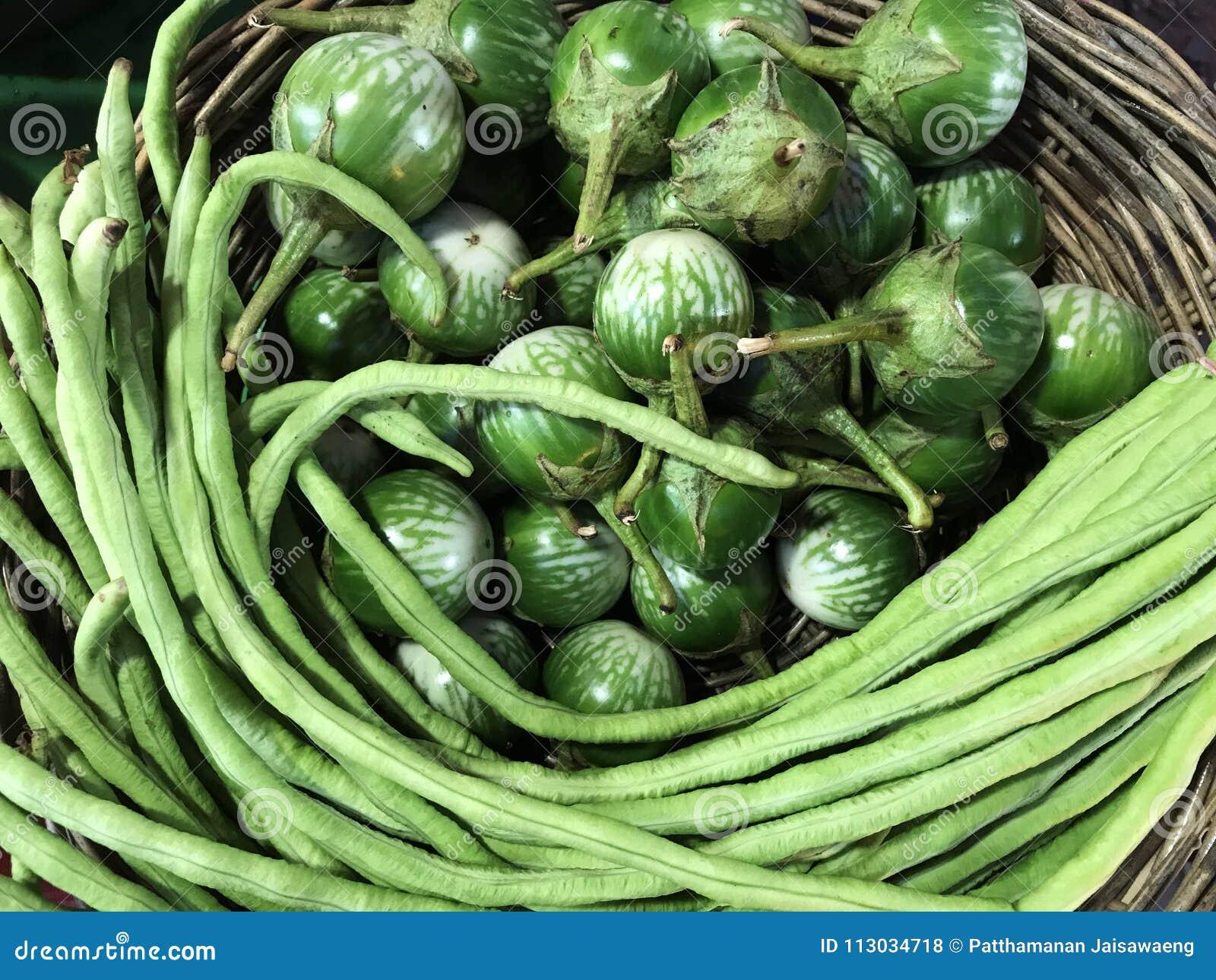 Berenjena y haba larga en cestas de mimbre en el mercado