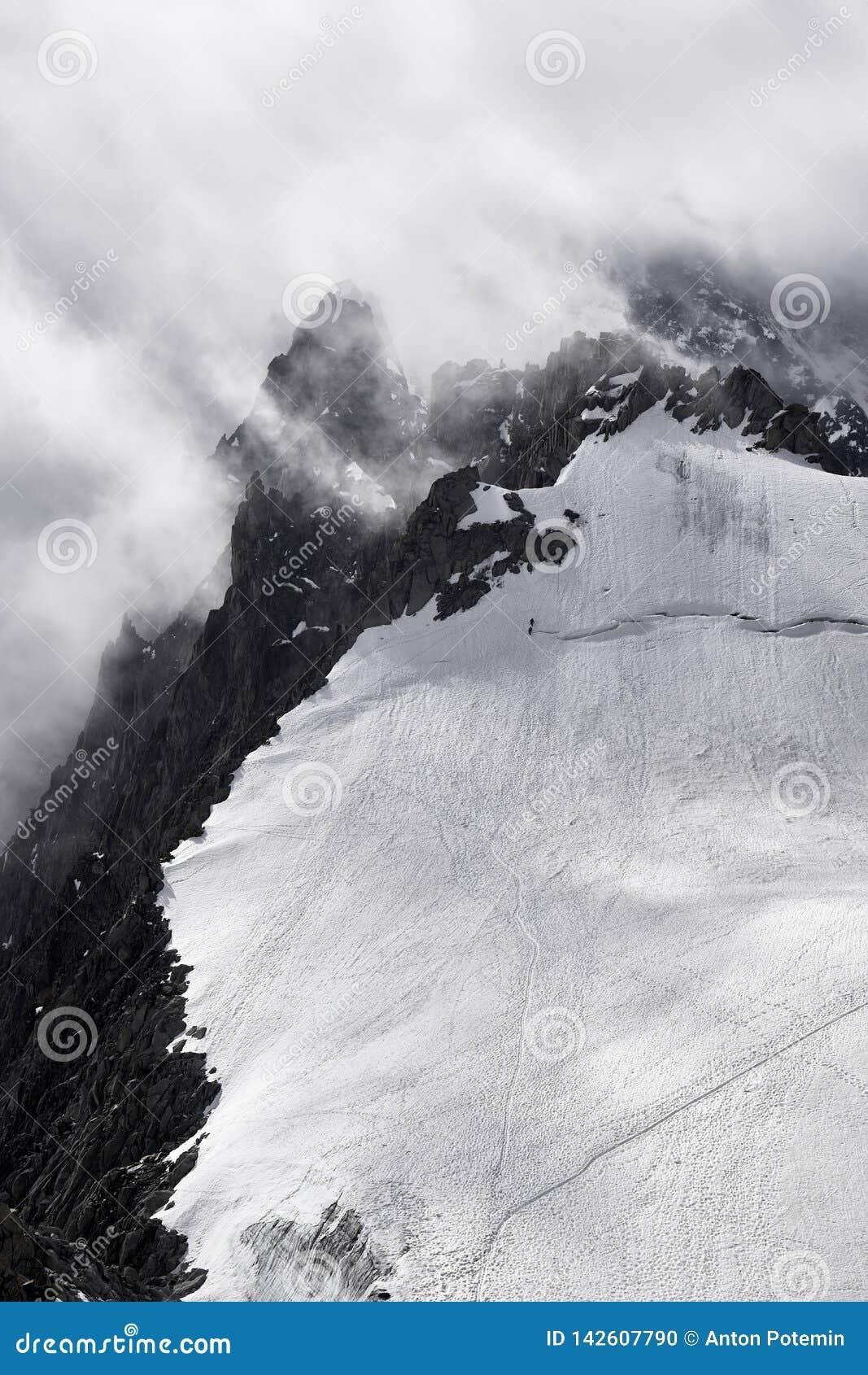 Berg i Chamonix i ett dåligt väder med klättrare
