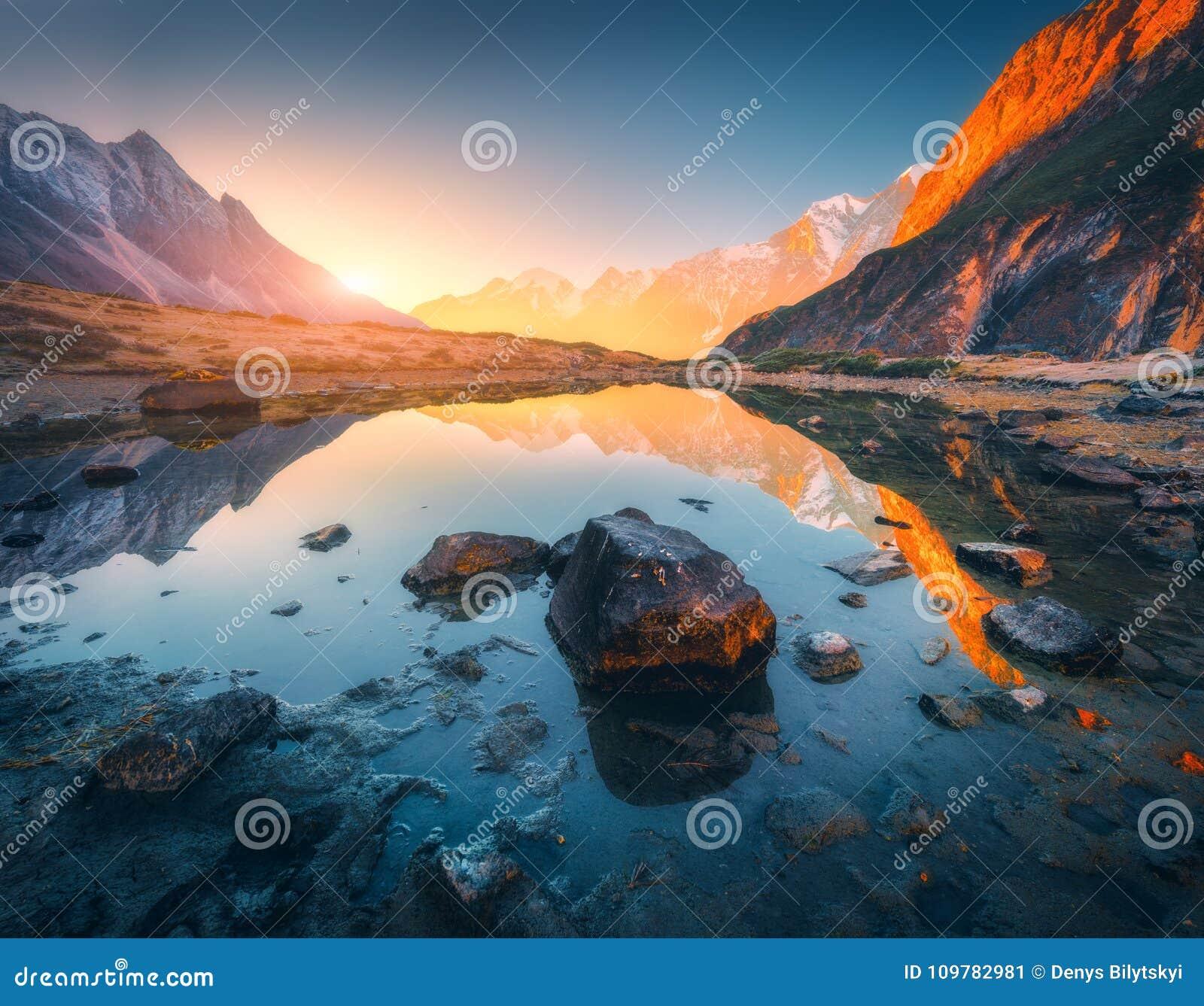 Berg med upplysta maxima, stenar i bergsjön på solnedgången