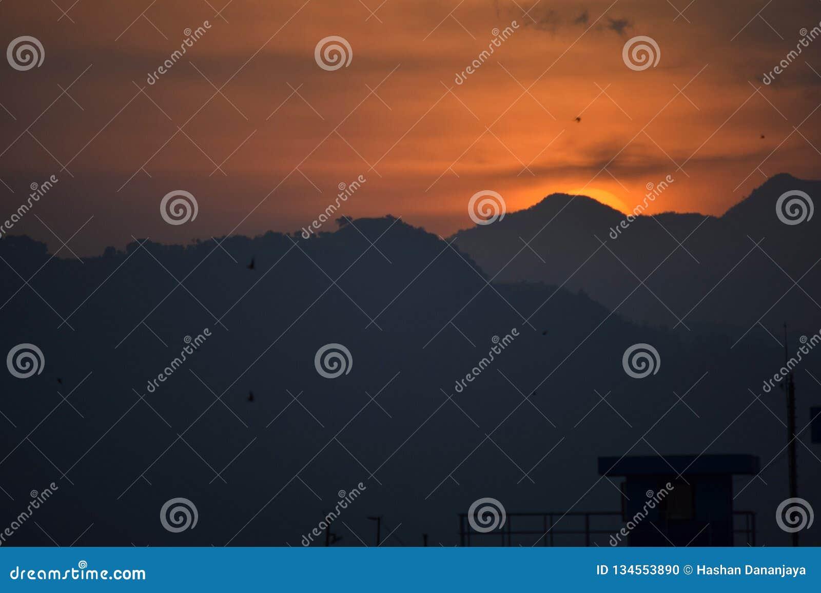 Berg och härlig solnedgång Udawalawa sjö