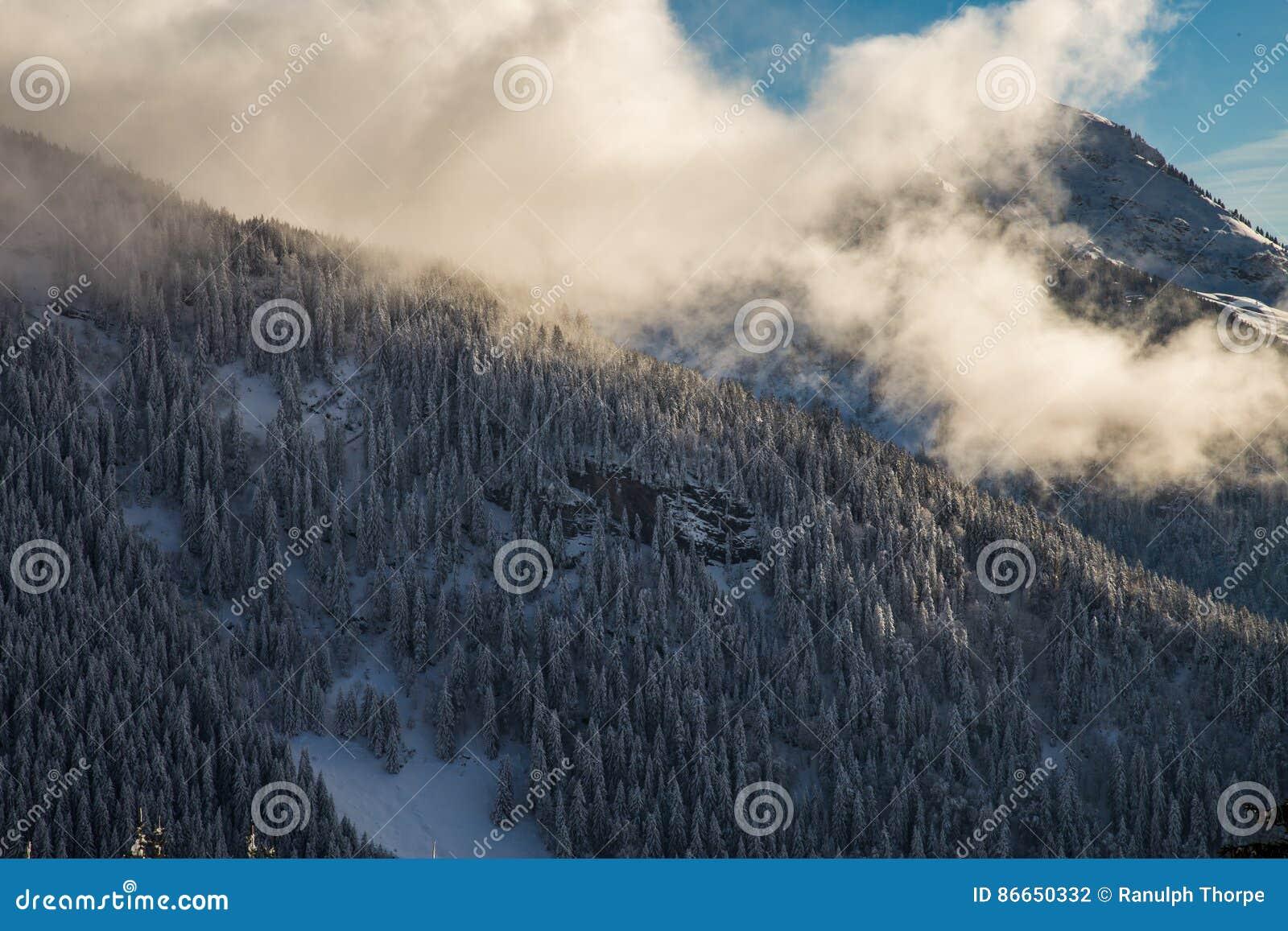 Berg som täckas med snö och omges av moln