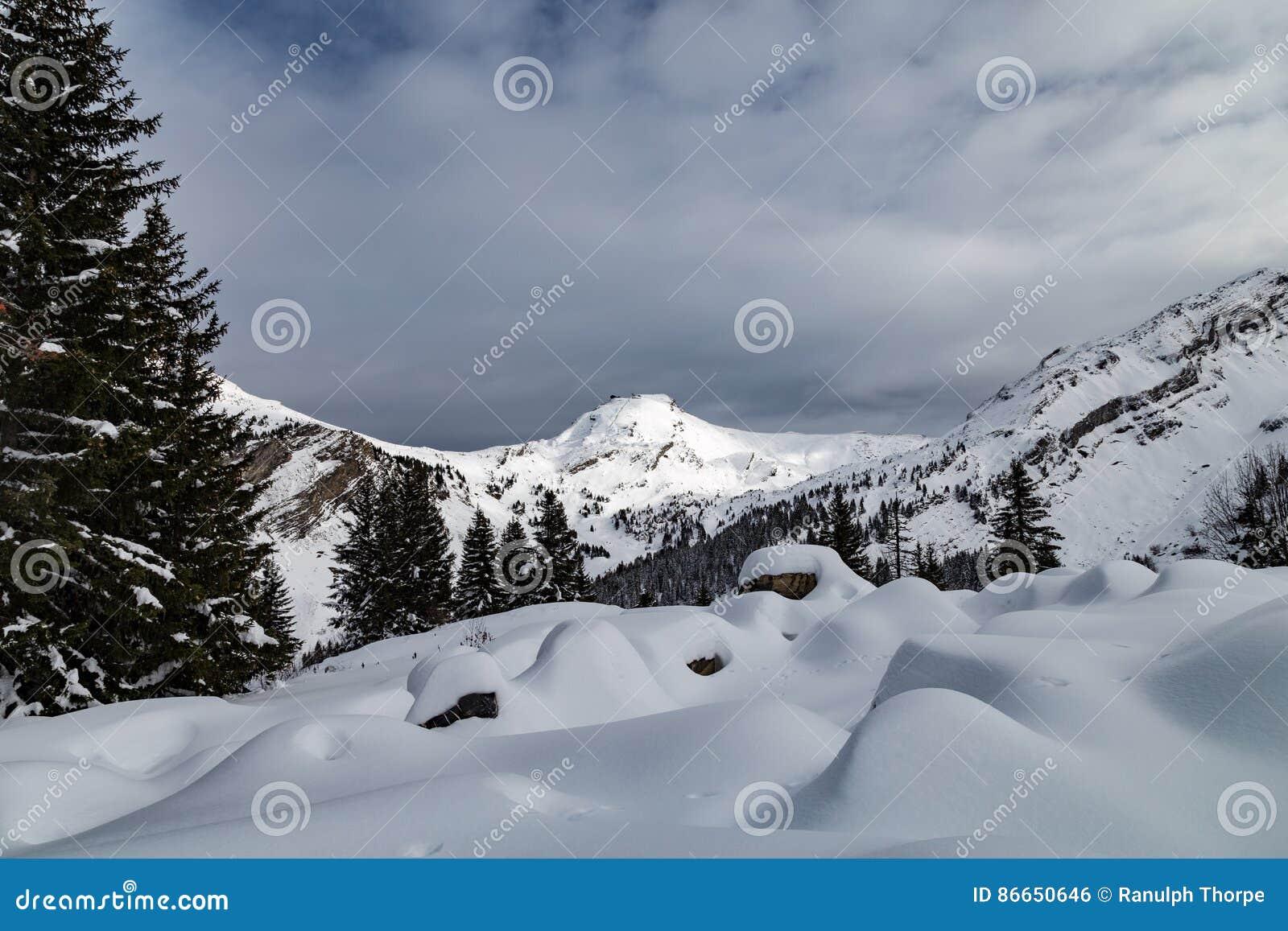 Berge bedeckt mit Schnee und durch Wolken umgeben