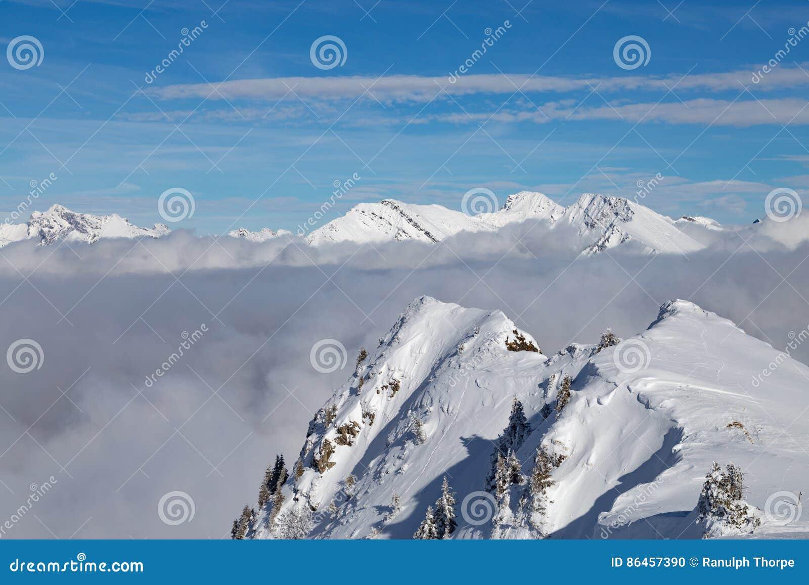Berge bedeckt mit Schnee und Wolken und Bäume