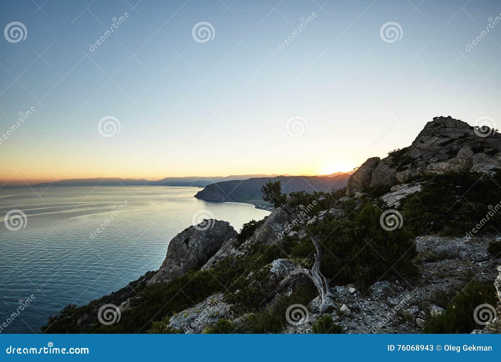 Bergen en overzees bij zonsondergang