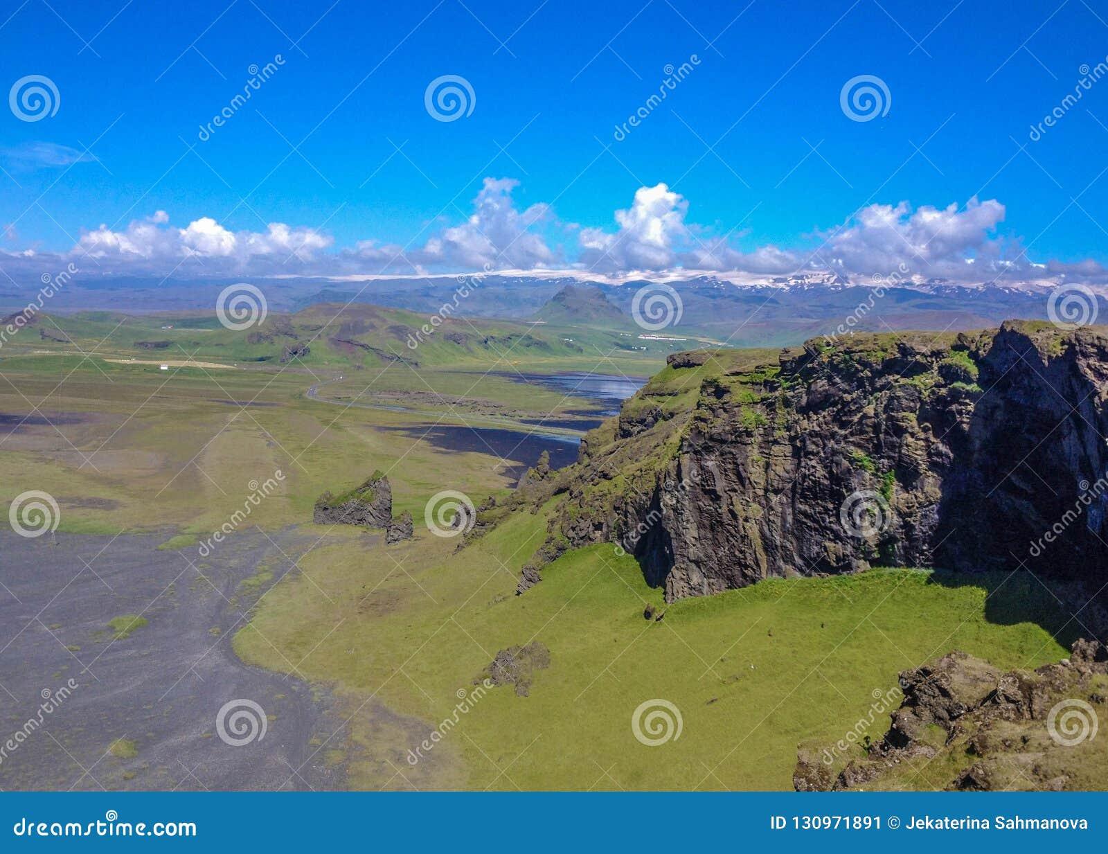 Bergen met groen mos, zwart zandstrand en witte oceaangolven op de achtergrond worden behandeld die Dyrholaey, Zuid-IJsland, Euro