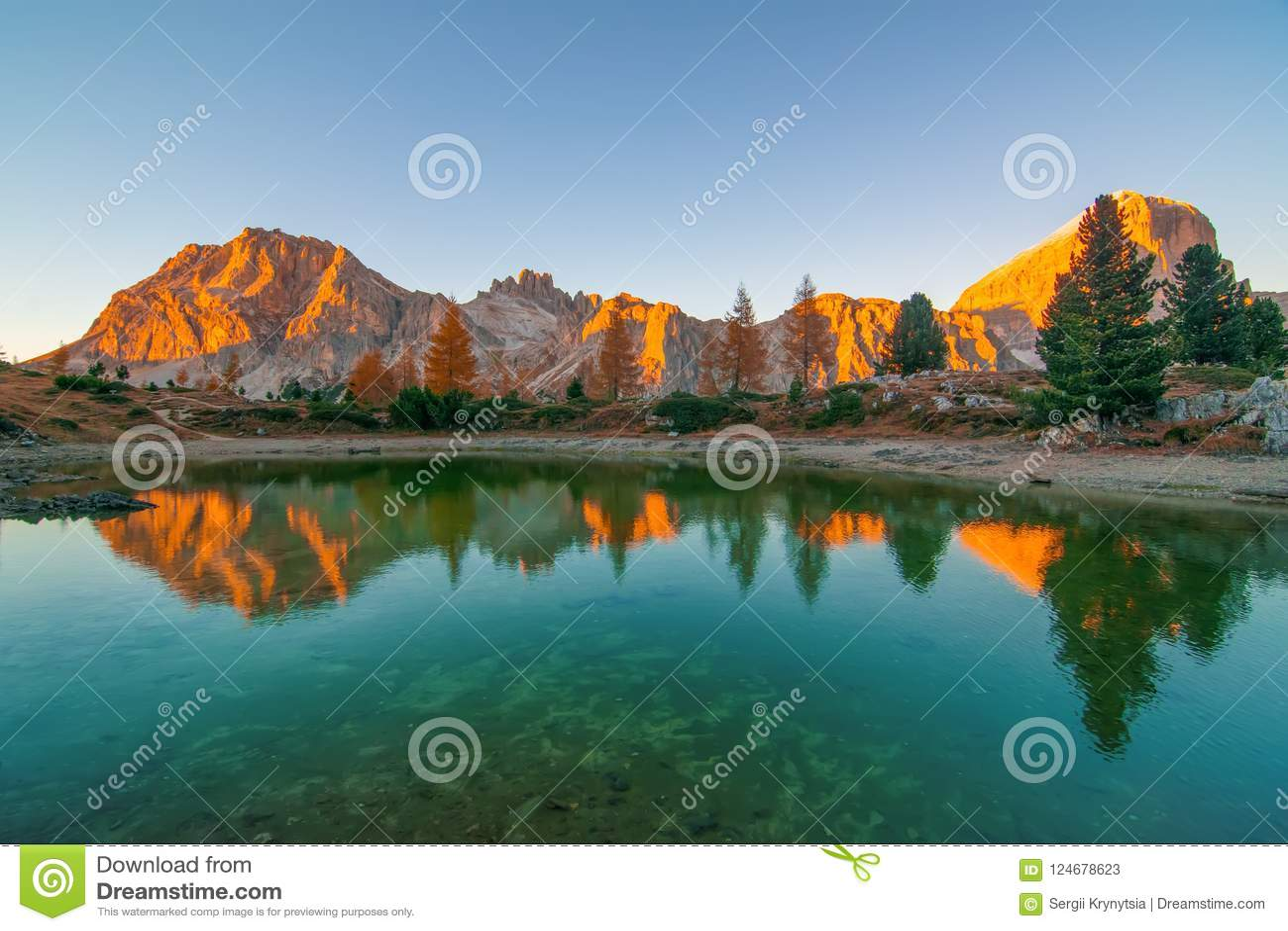 Berget vaggar och höstträd reflekterade i vatten av Limides sjön på solnedgången, Dolomitefjällängar, Italien