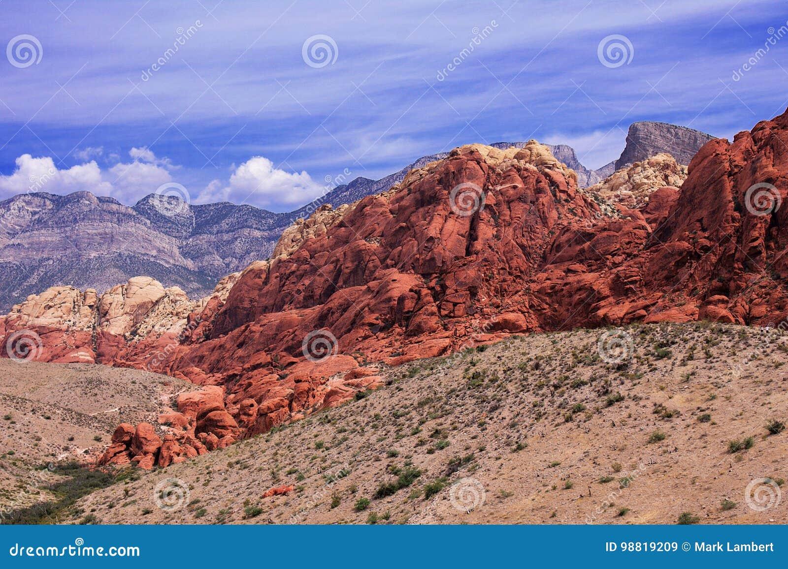 Bergketens in Rode Rots, Nevada De rotsen zijn levendige rode, oranje en donkere bruin, en tonen tekens van zware erosie De hemel