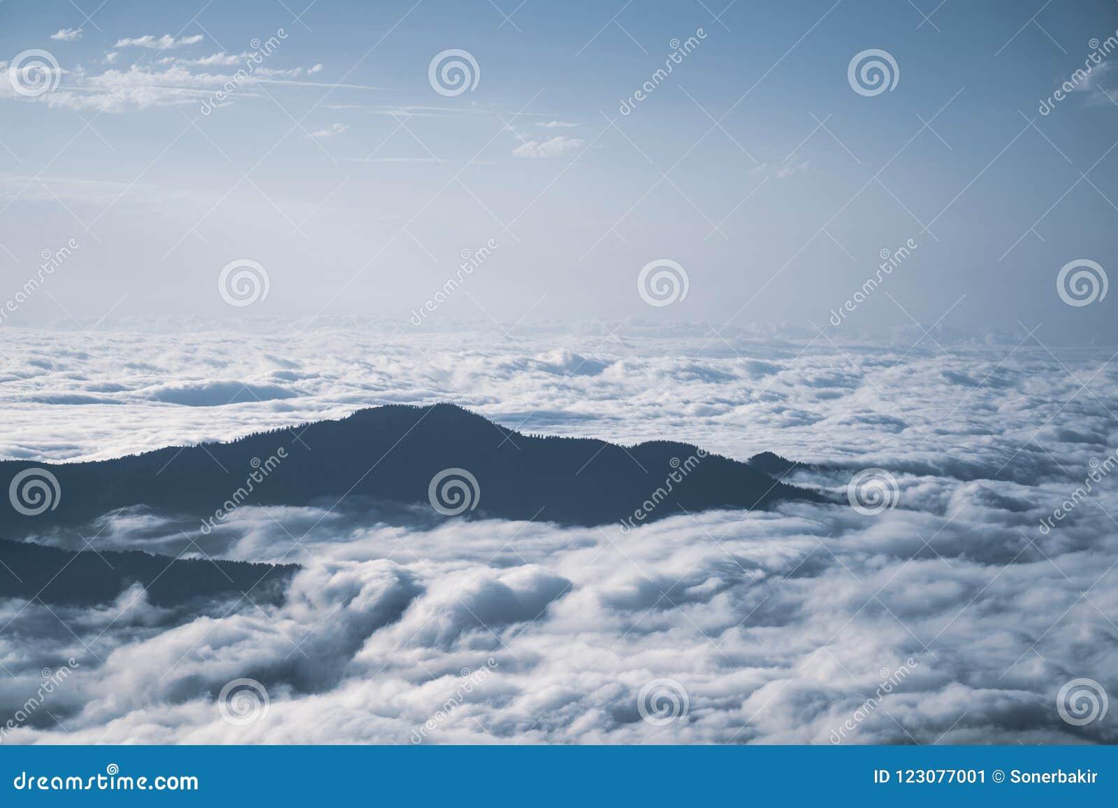 Bergkonturn ovanför molnen på soluppgång, beskådar uppifrån sikt av berg