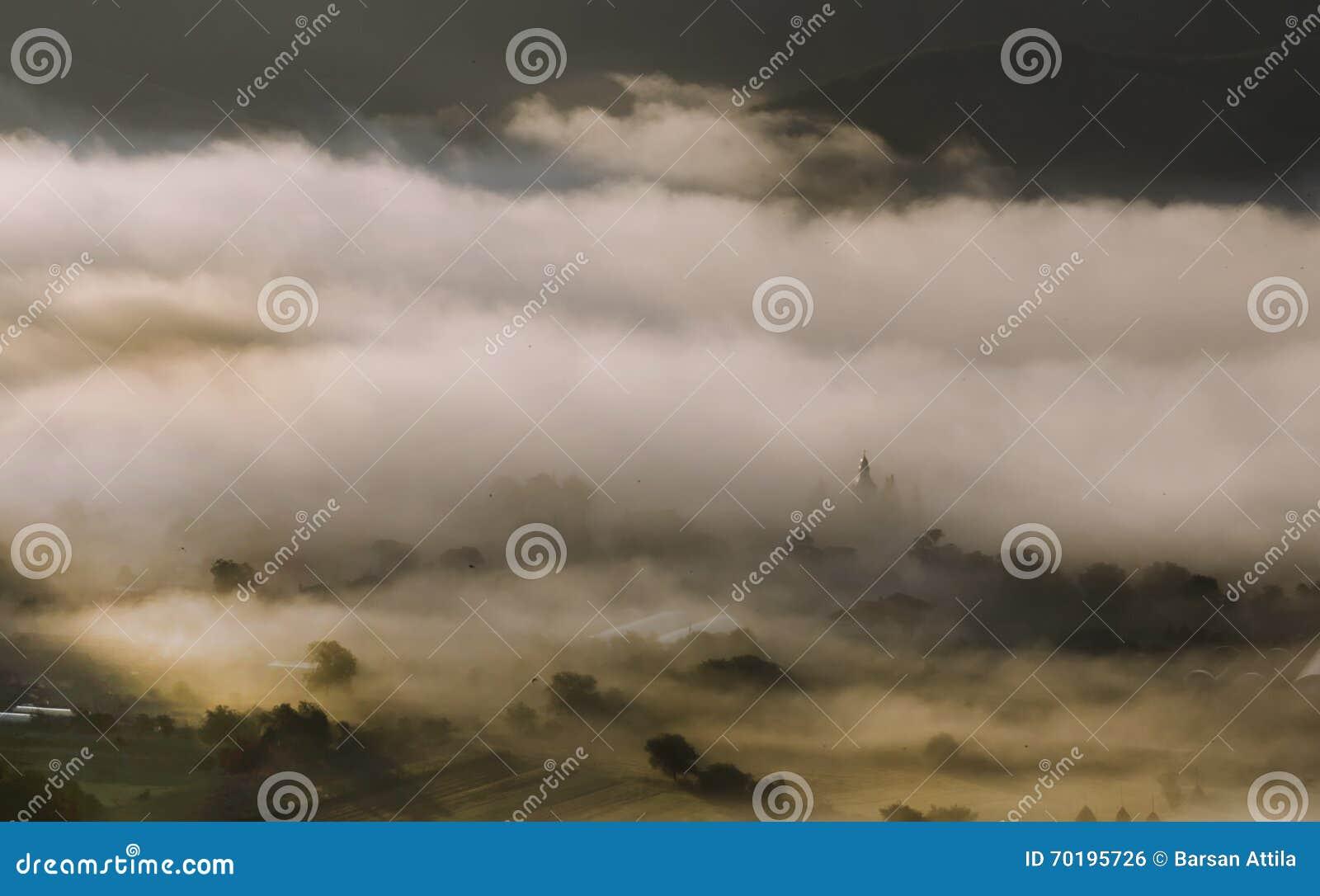 Berglandskap med sommarmorgondimma på soluppgång