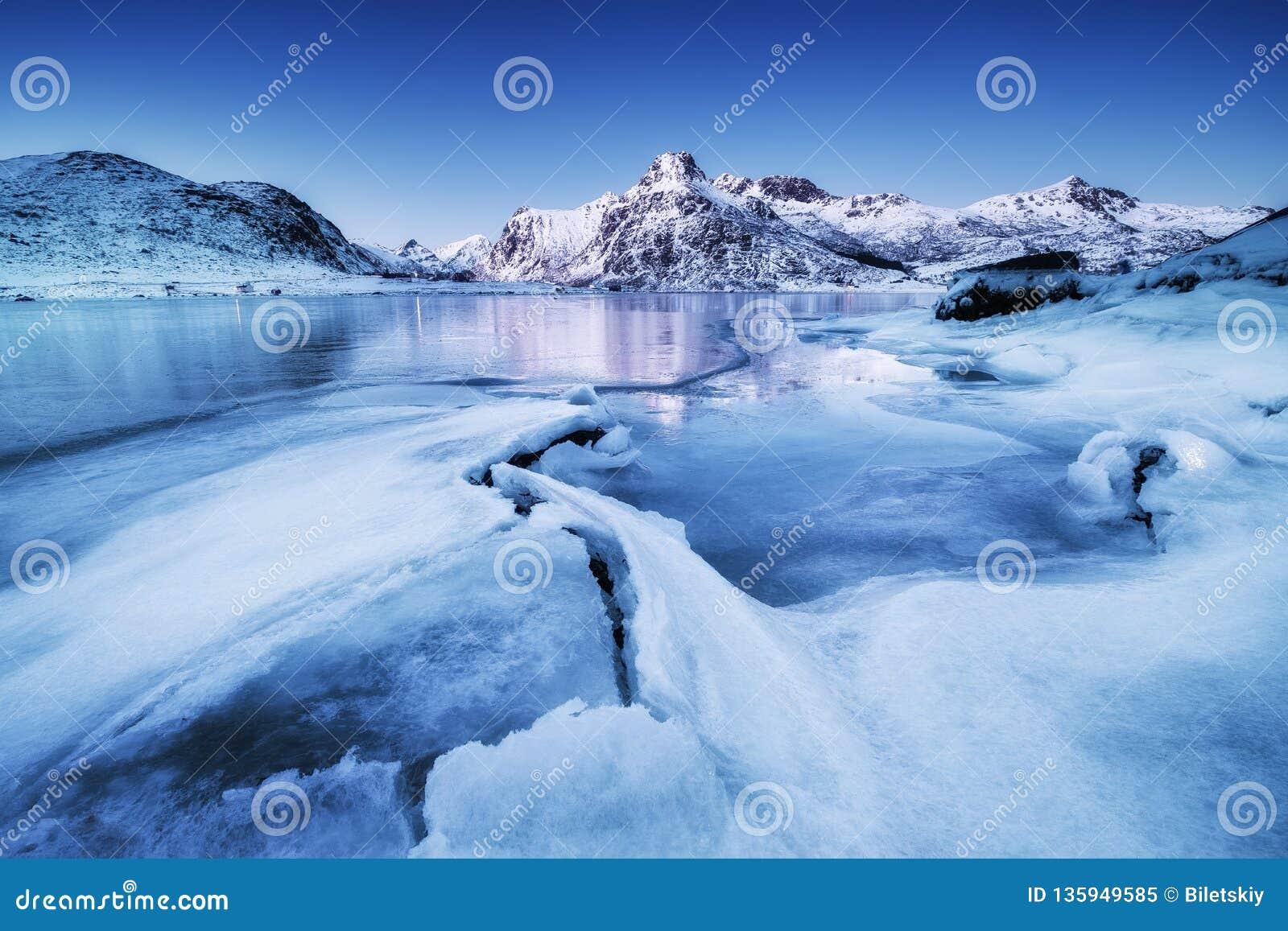 Bergrand en ijs op de bevroren meeroppervlakte Natuurlijk landschap op de Lofoten-eilanden, Noorwegen
