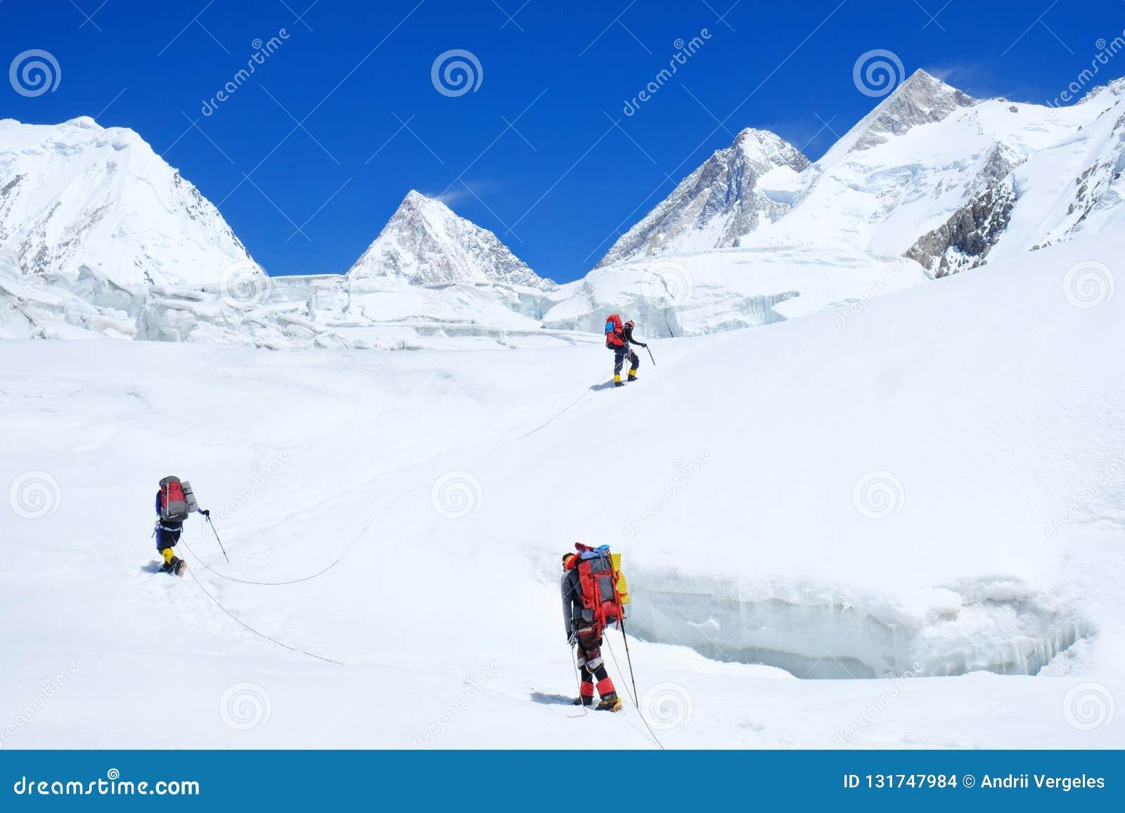 Bergsteiger reache der Gipfel der Bergspitze Bergsteiger drei auf dem Gletscher Erfolg, Freiheit und Glück, Leistung in den Berge