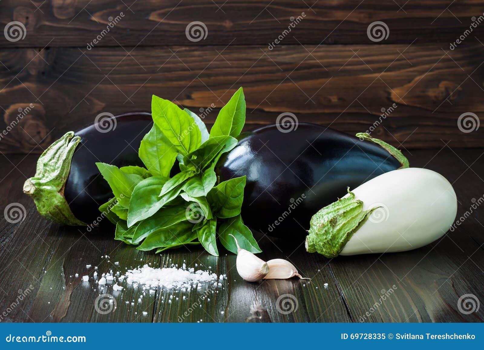 Beringela roxa e branca (beringela) com manjericão e alho na tabela de madeira escura Vegetais crus frescos da exploração agrícol