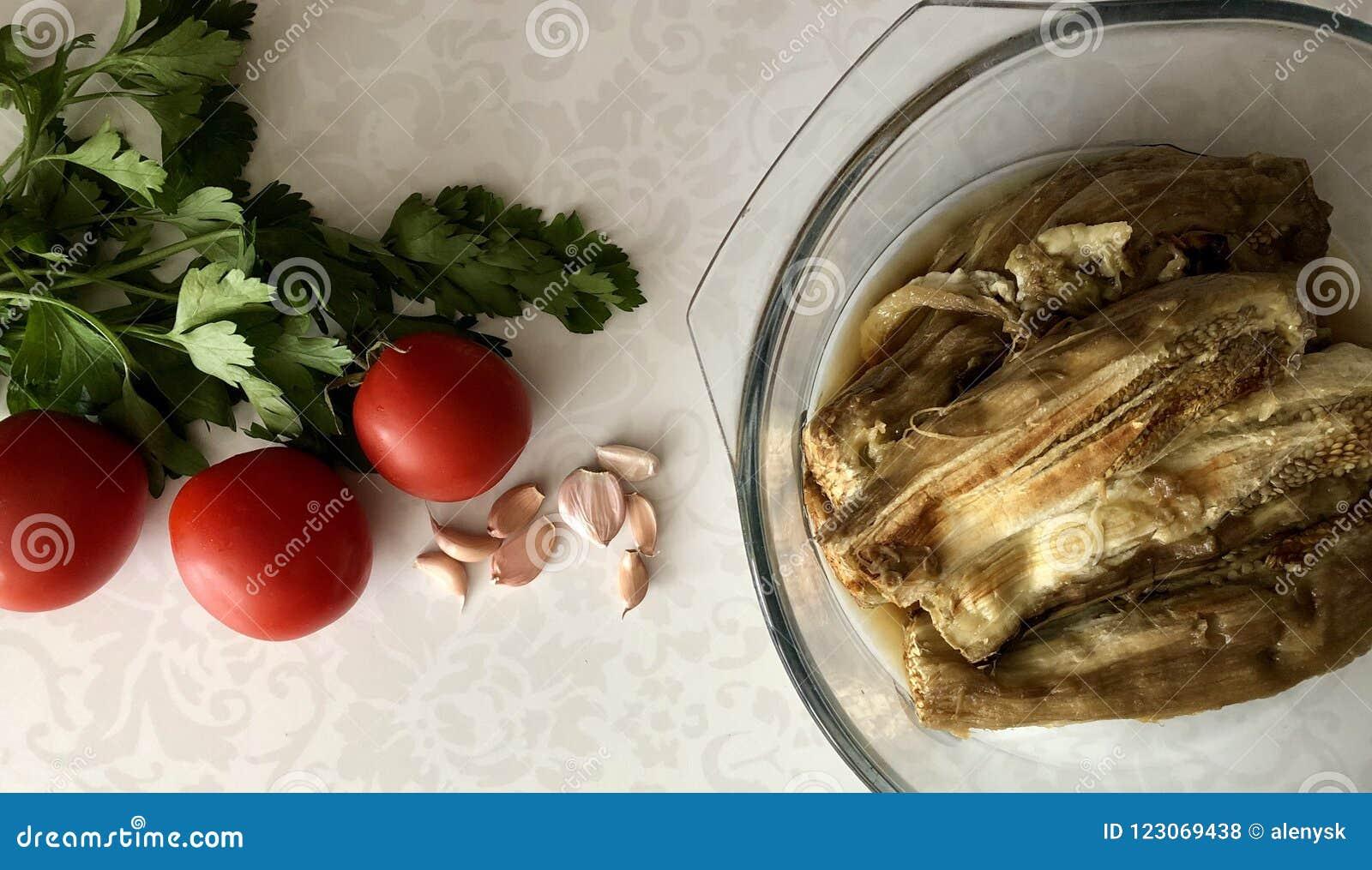 Beringelas cozidas em uma bacia de vidro, em uns tomates frescos, em uma salsa do greem e em um alho