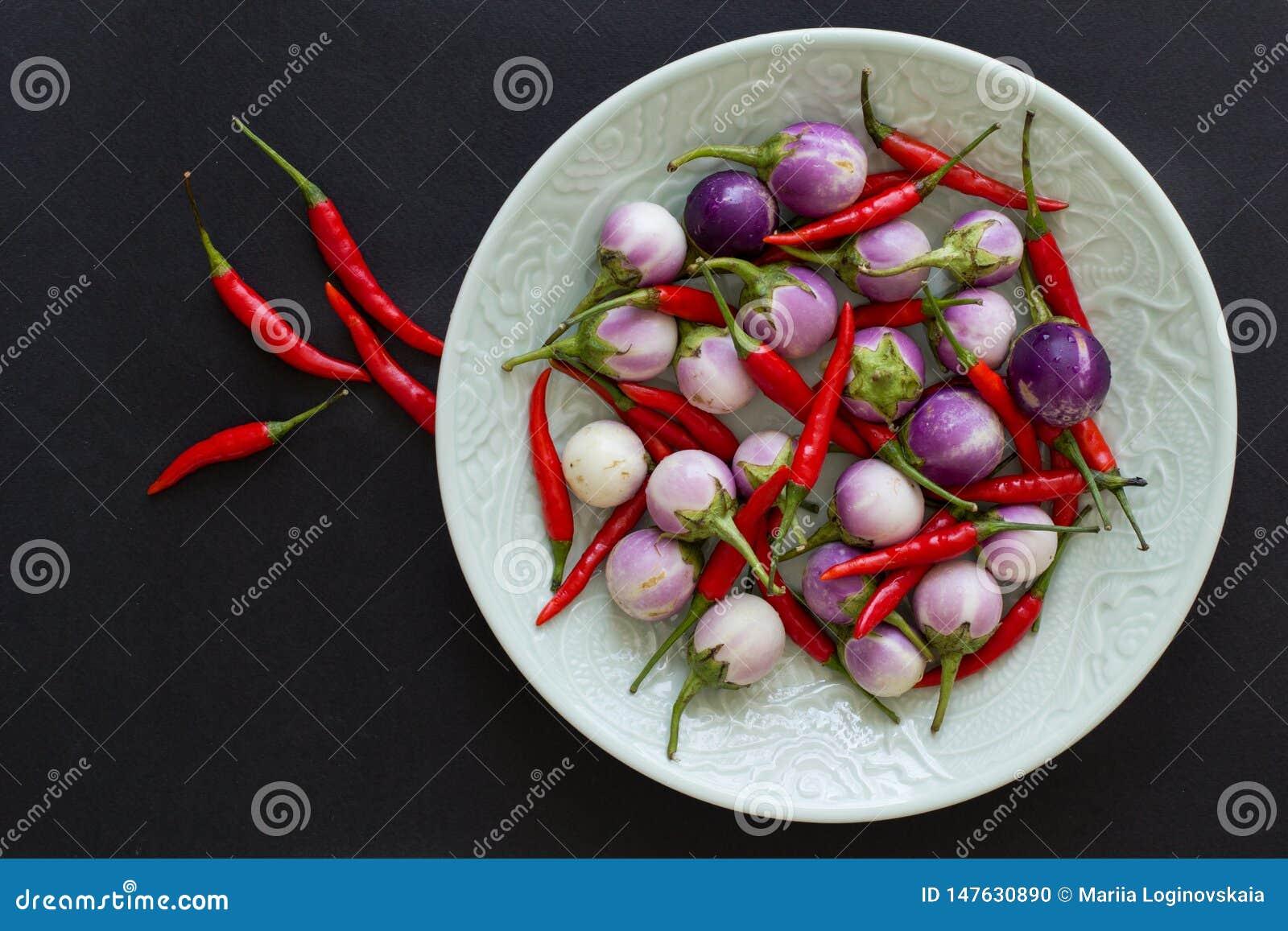 Beringelas e pimentas da malagueta picante em uma placa verde e próximo tailandeses roxos em um fundo preto Alimento asi?tico