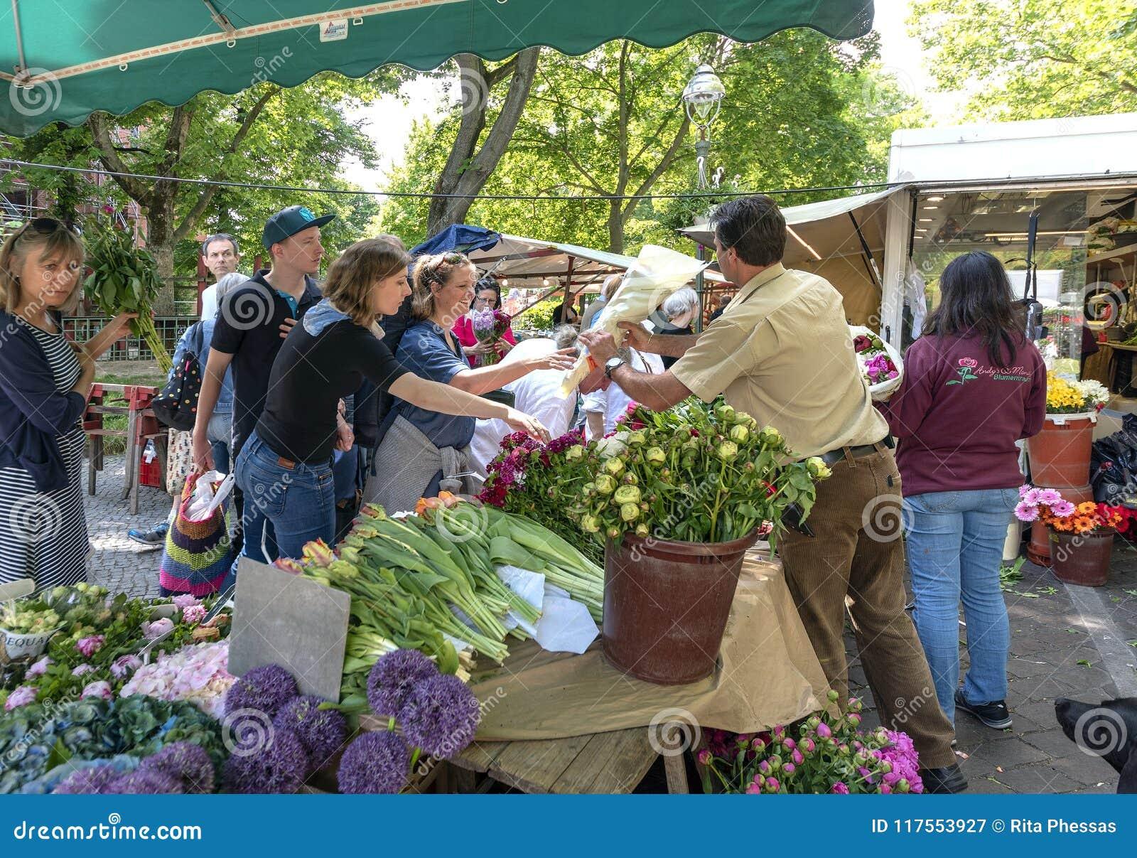 Berliński Niemcy A kwiatu 19-5-2018 mężczyzna w jego kramu na rynku sprzedaje jego kwiaty jego klienci na pogodnym ciepłym dniu,