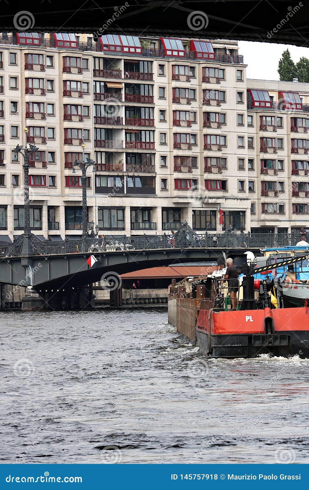 Berlijn, Duitsland, 13 Juni 2018 Boot die de rivier navigeren Op de achtergrond een brug en woningbouw