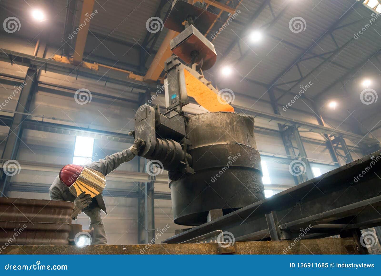 Berlim, Alemanha - 18 de abril de 2013: Produção de componentes do metal em uma fundição - grupo de trabalhadores