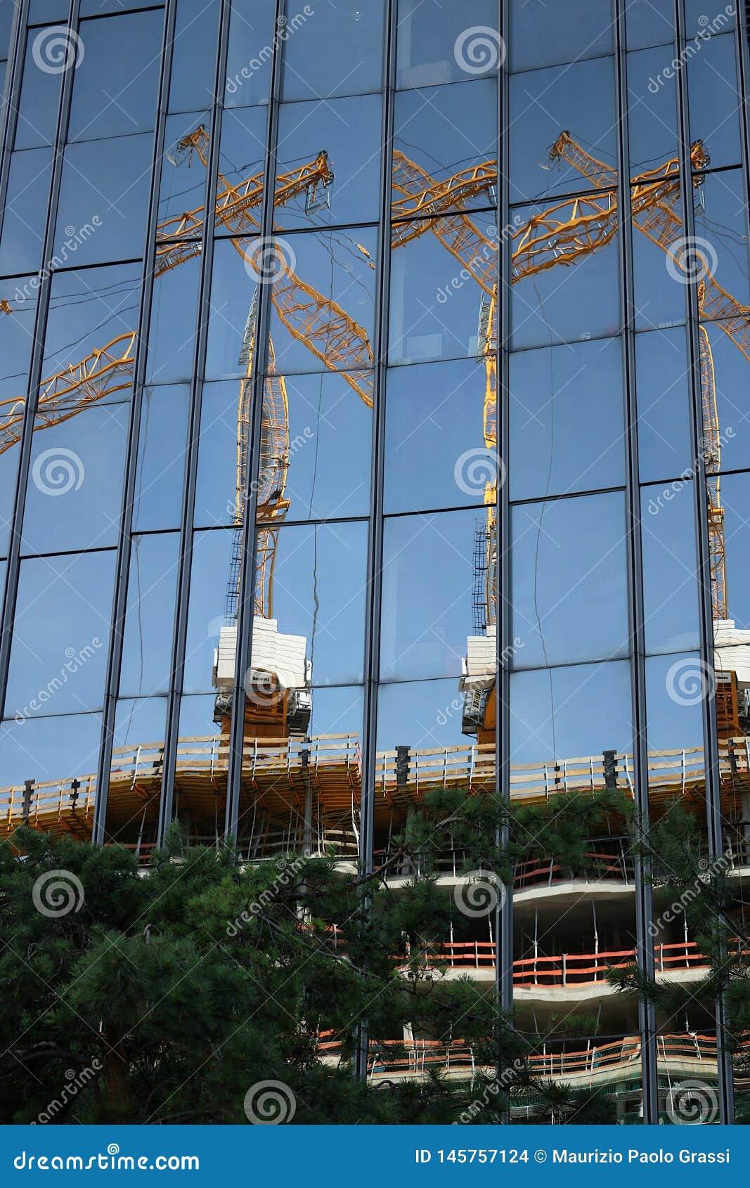 Berlim 06/14/2008 Fachada de vidro de uma constru??o com reflex?o de um canteiro de obras Guindastes e andaime